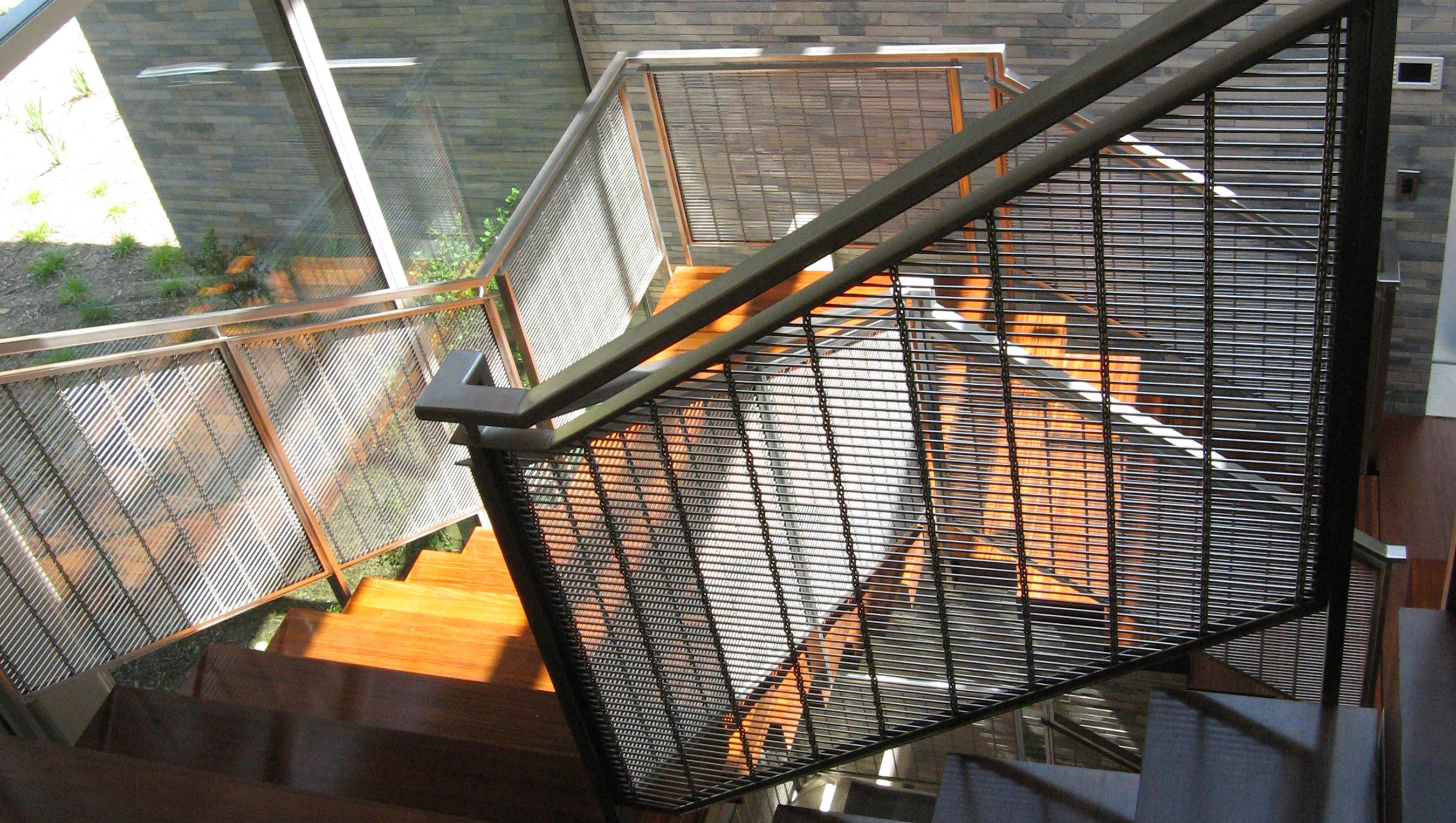 Decorative mesh, M13Z-145, adds a modern flair to the railing infill panels of this residence.