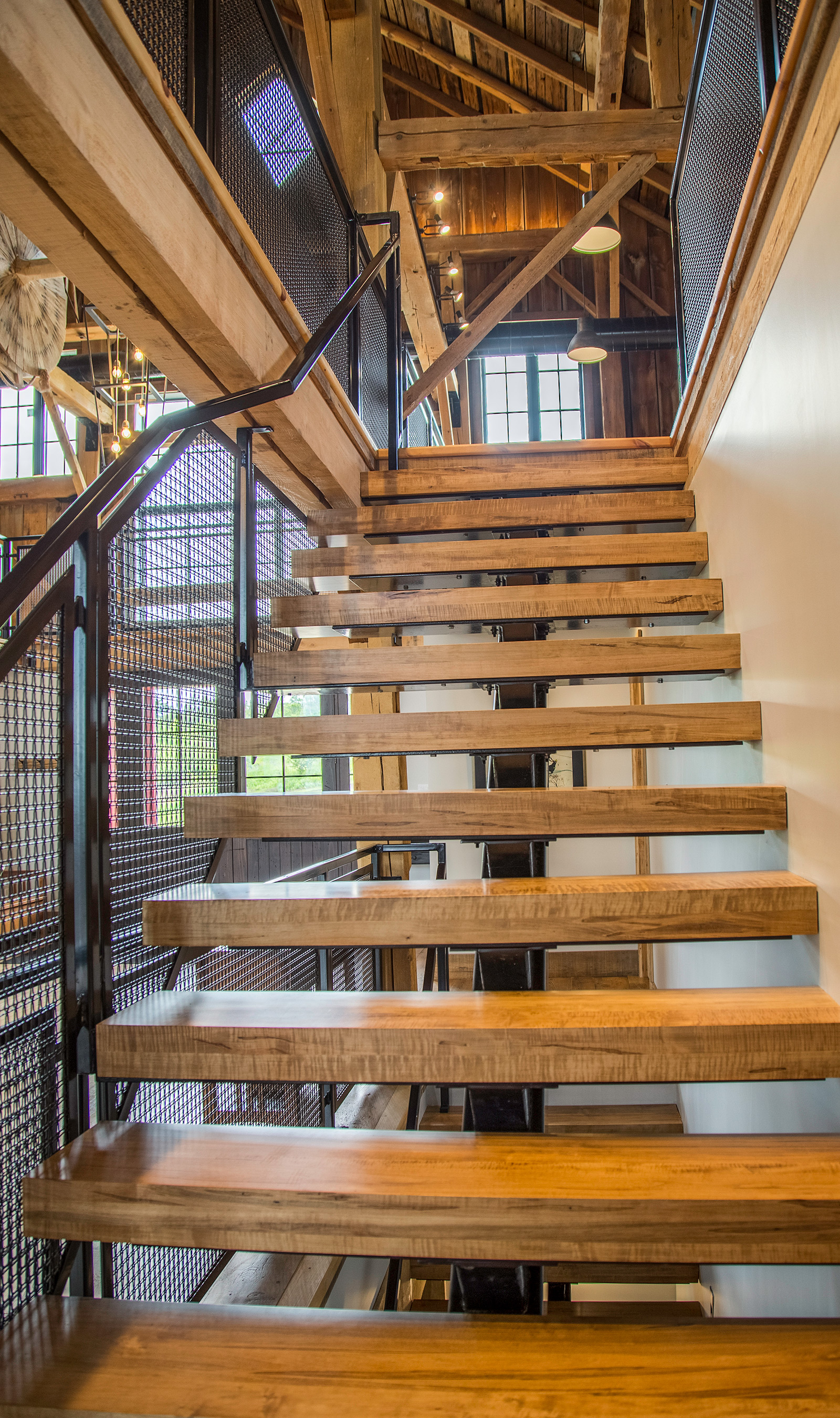 Looking up staircase with wire mesh