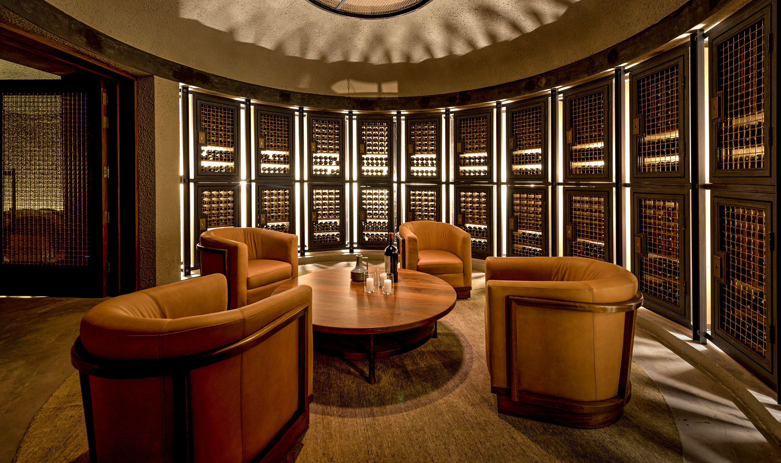 In an exclusive club area, Banker Wire's L-62 woven wire mesh in bronze is utilized as cabinetry protecting various bottles of wine.
