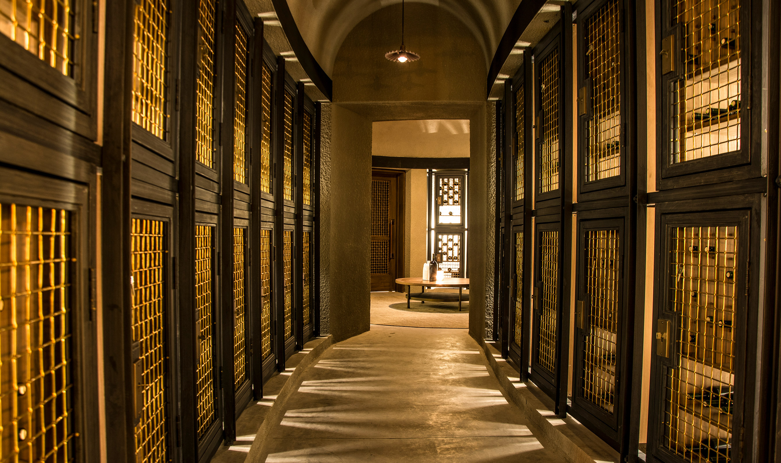 Bronze woven wire mesh integrated into wine lockers adds a warmth to the stone hallway.