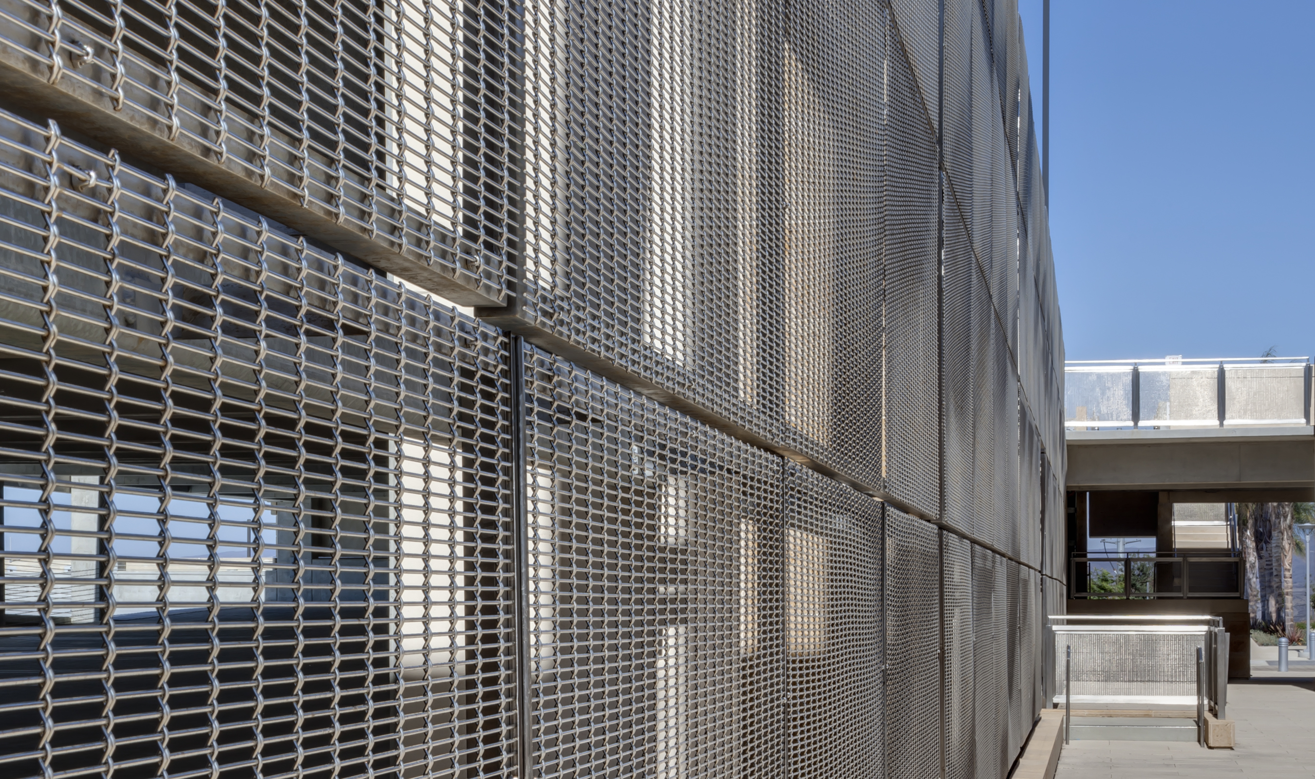 The rectangular openings in the FPZ-10 pattern allow natural light transmission, and the stainless steel metal fabric picks up the stairwells' blue and green hues.