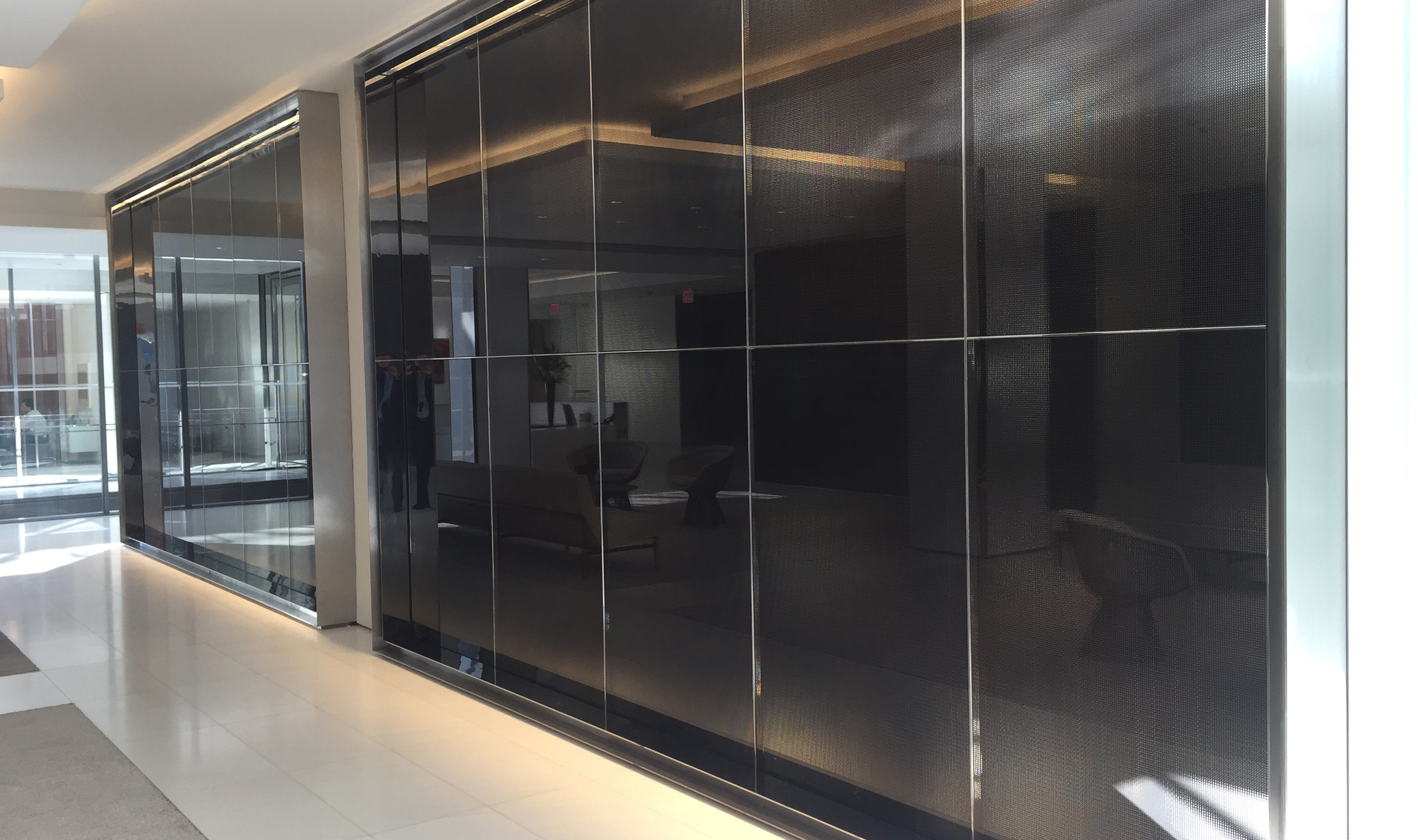 Banker Wire S-12 mesh sandwiched in glass encloses a conference room.