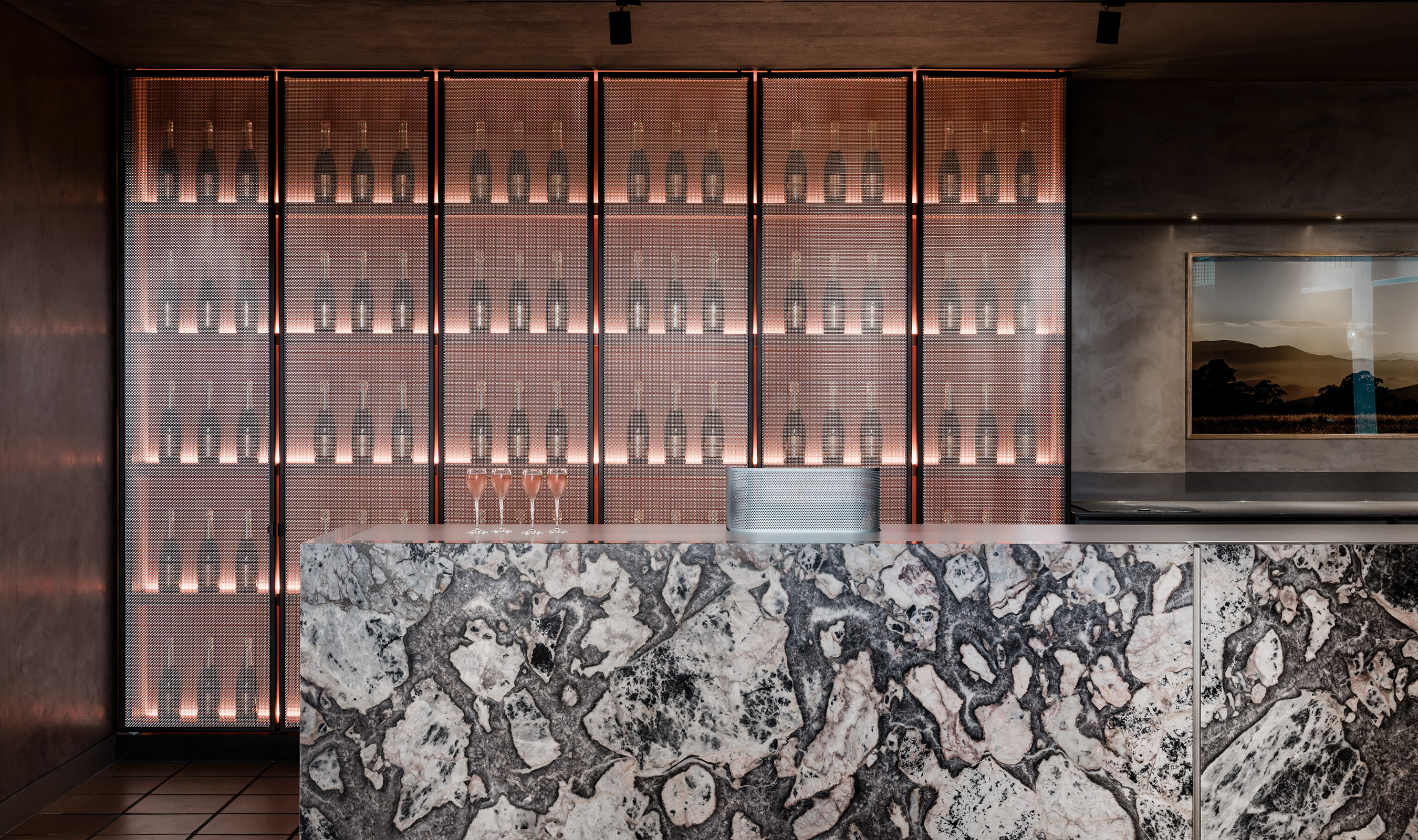 The blush color of the shelving and the wine within the bottles is beautifully complimented by the sparkle of the stainless steel - appearing as bubble would within the champagne and wine.