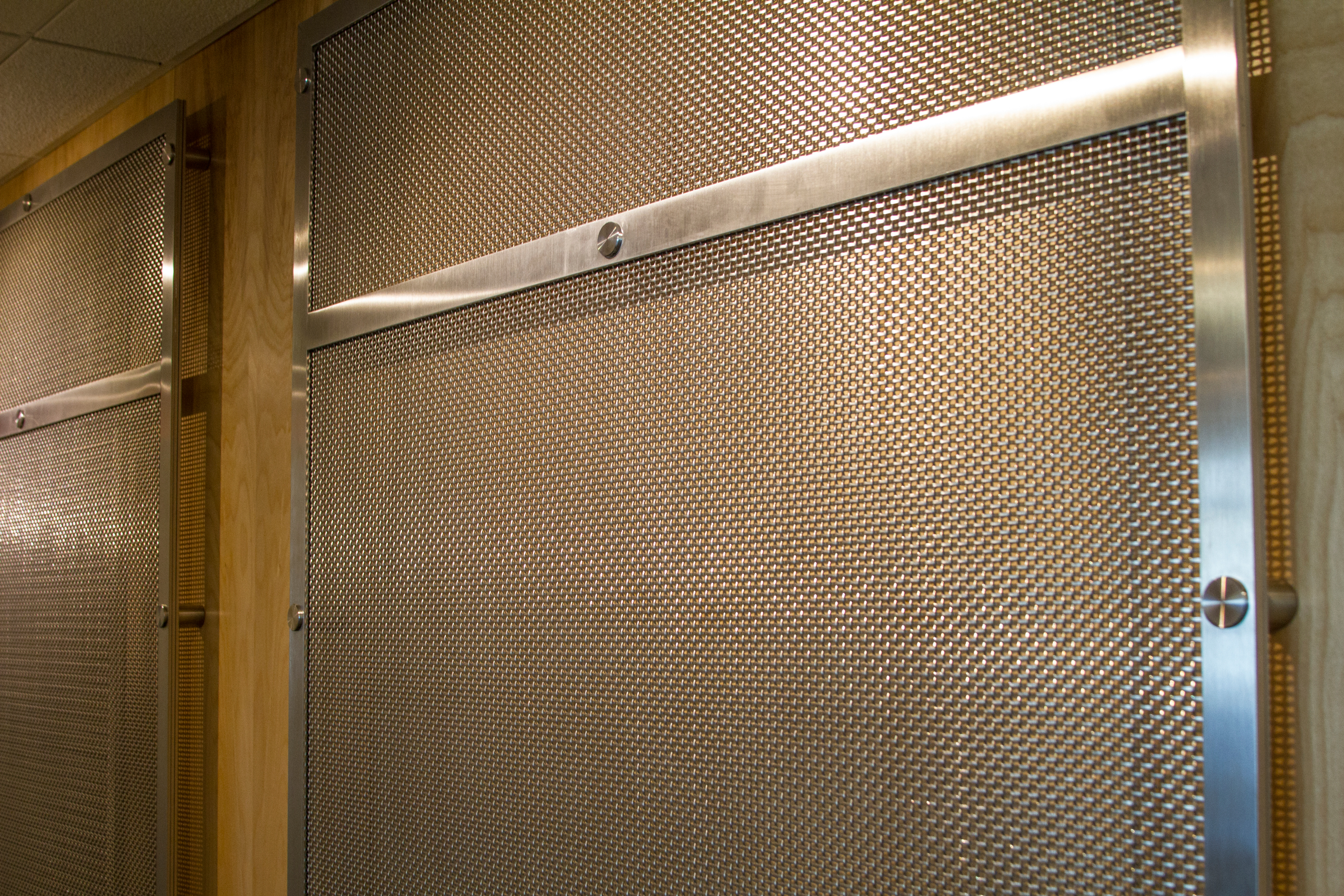 Banker Wire mesh allows the warmth of the wood paneling to show through.