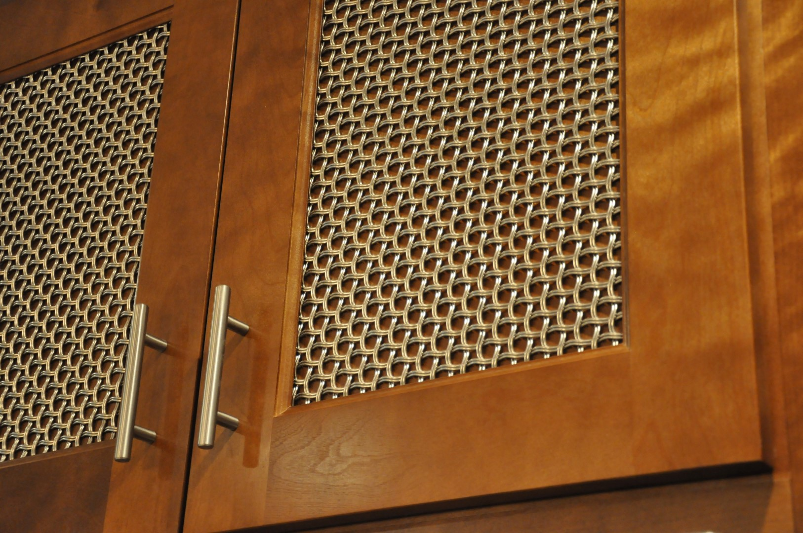 Woven wire mesh over wood inserts conceals the items within the cabinets for a neat appearance.
