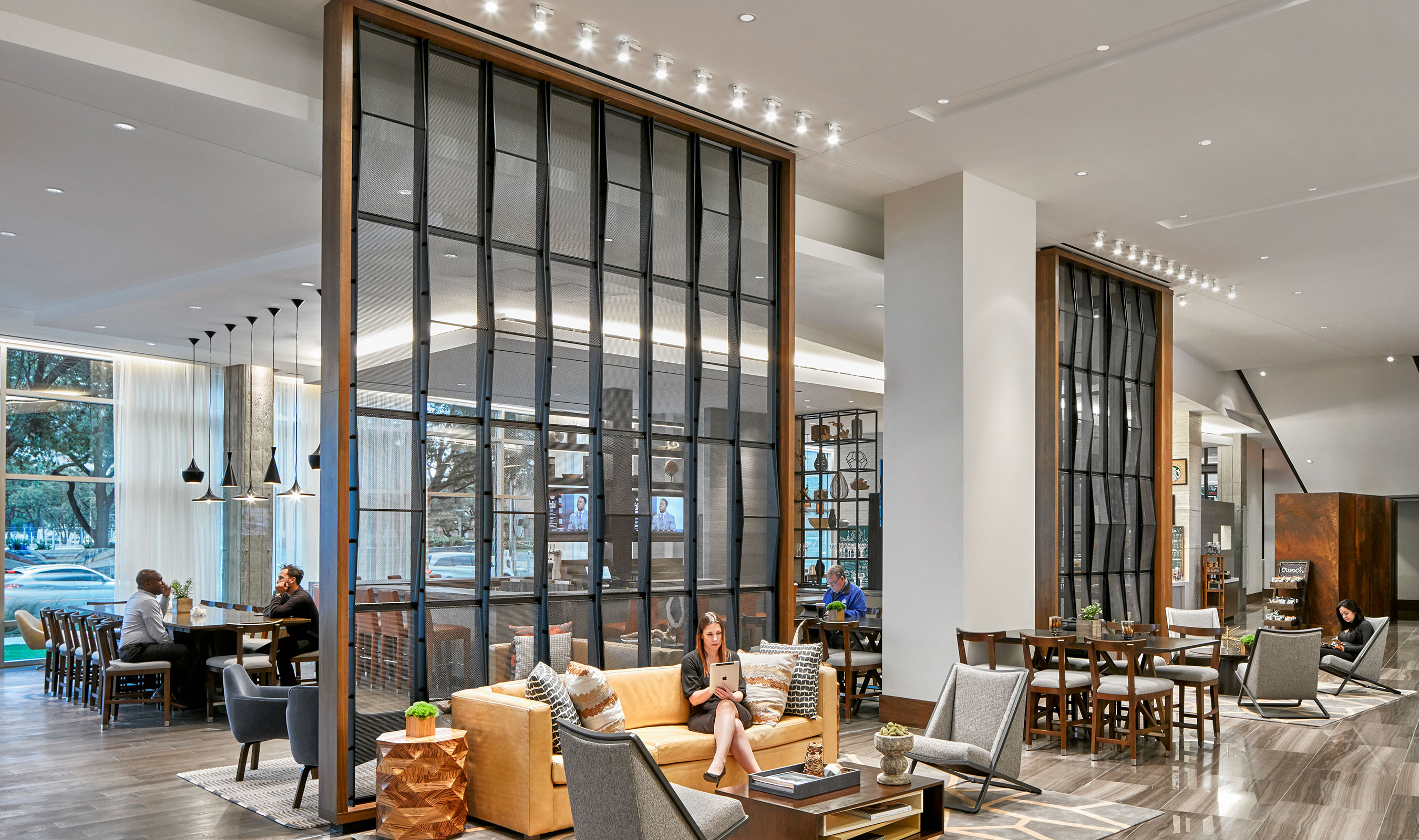The open, multi-function lobby serves as a workplace, social gathering area and relaxing living room with a bar, lounge, market and formal dining divided my a screen made from Banker Wire architectural wire mesh.