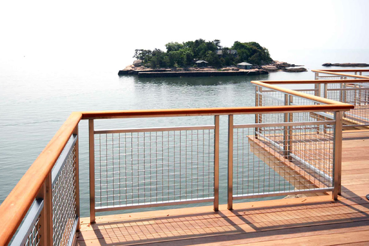 The stainless steel of the decorative mesh railing infill is a compliment to the wood deck of this Island Getaway.