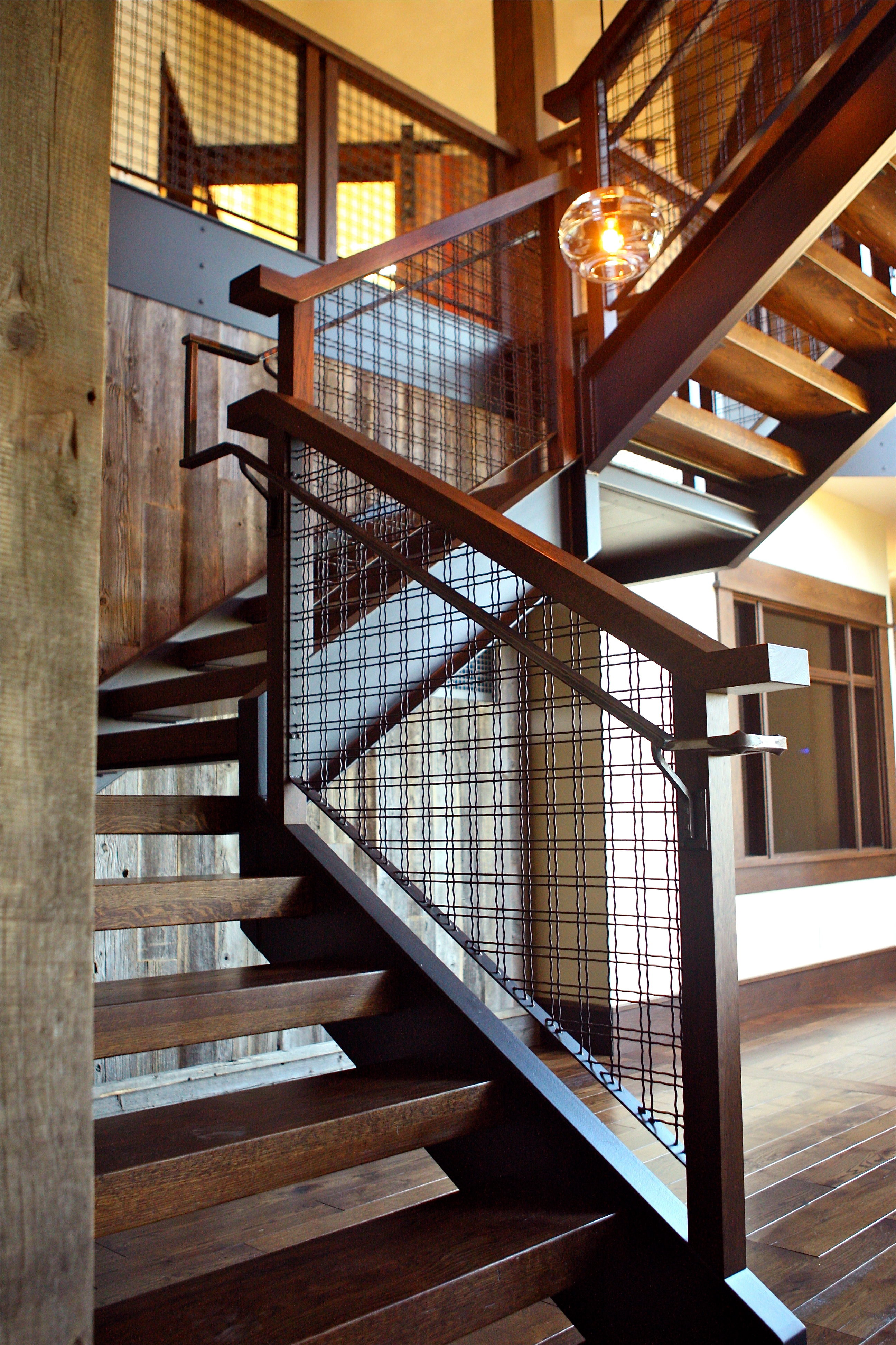 M22-8 architectural woven wire mesh infill on this staircase maintains the uninterrupted sight lines in this home.