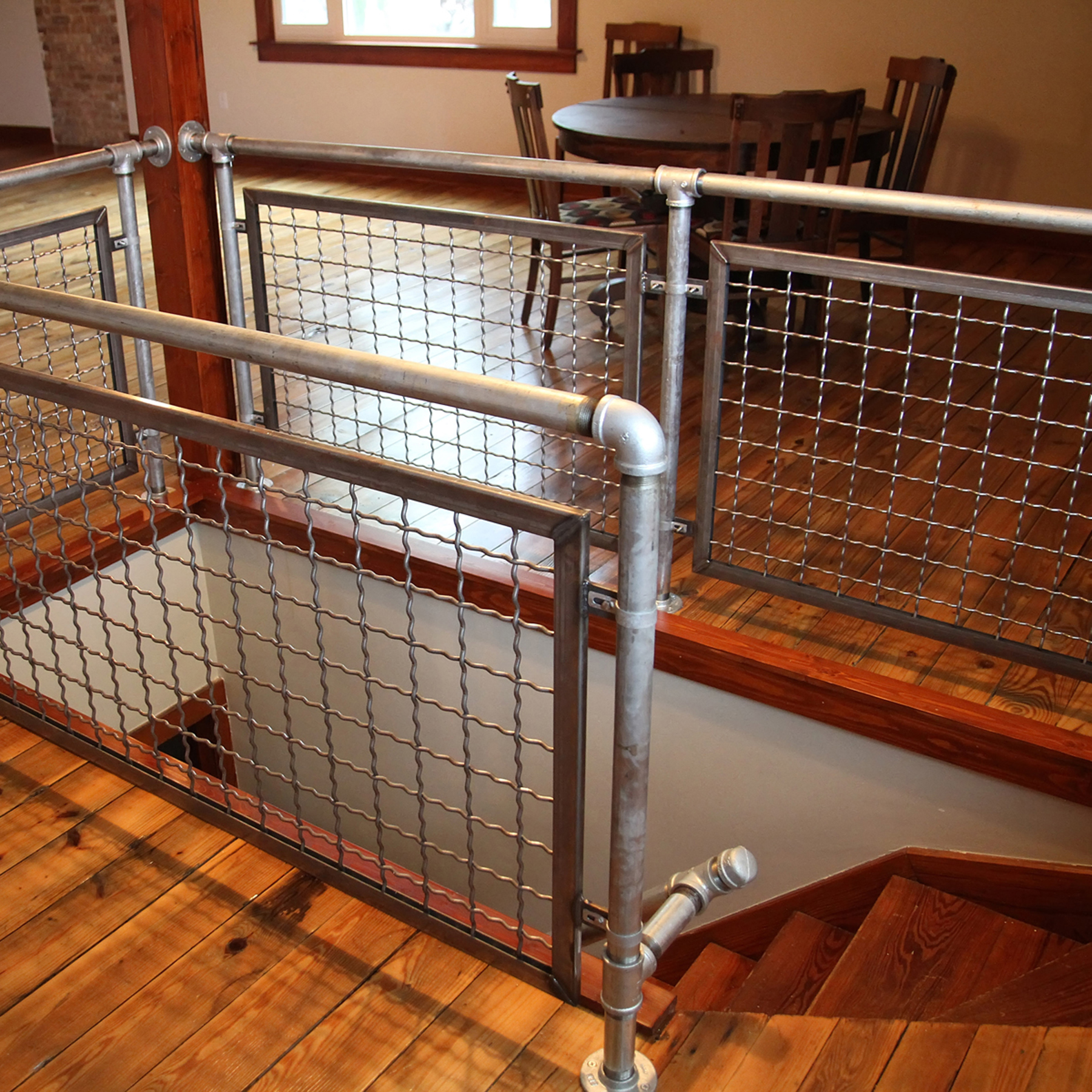 The Banker Wire mesh and U-edge frame harmonize visually with the weathered steel railing and reclaimed barn wood stair treads