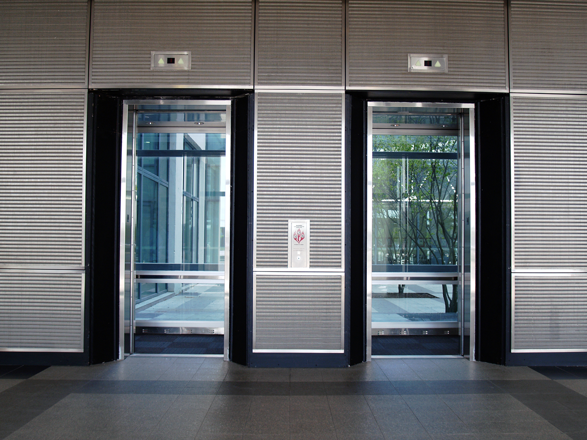 The consistent large diameter opaque woven wire mesh surface creates a horizontal flow that contrasts with the tall elevator openings.