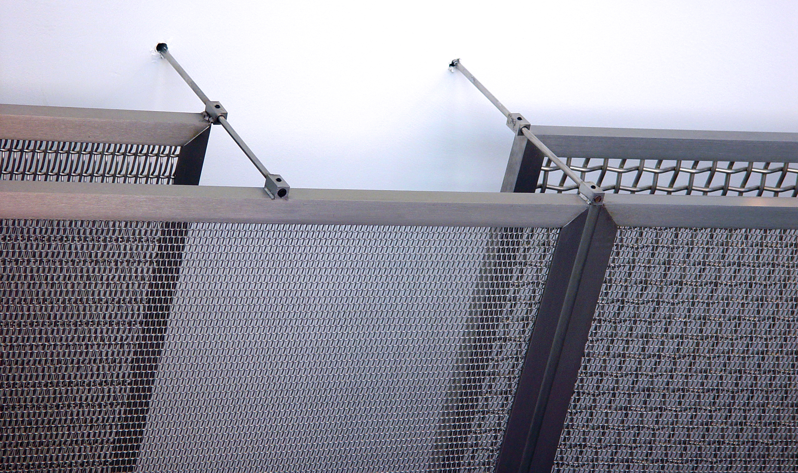 This custom ceiling uses stainless angle iron frames with the woven wire mesh welded to the back side.