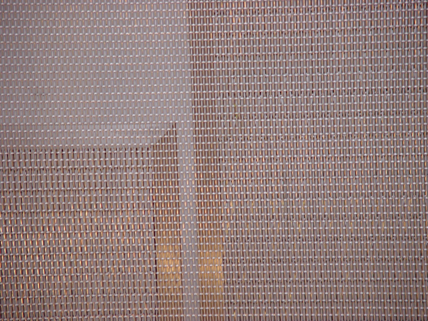Heavy woven wire mesh is visible through the finer weaves below.