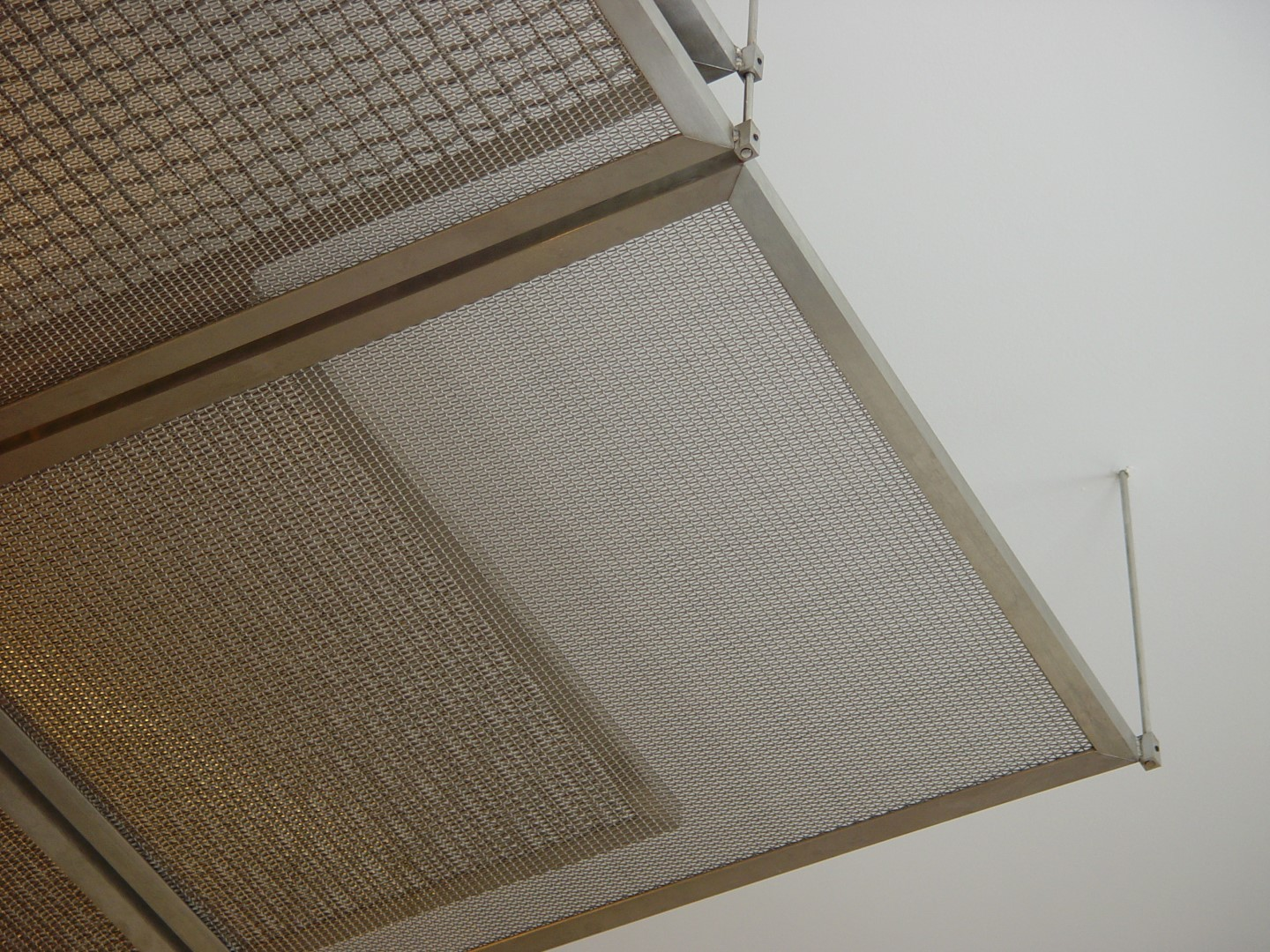 Layers of woven wire mesh are visible because of differences in opacity.