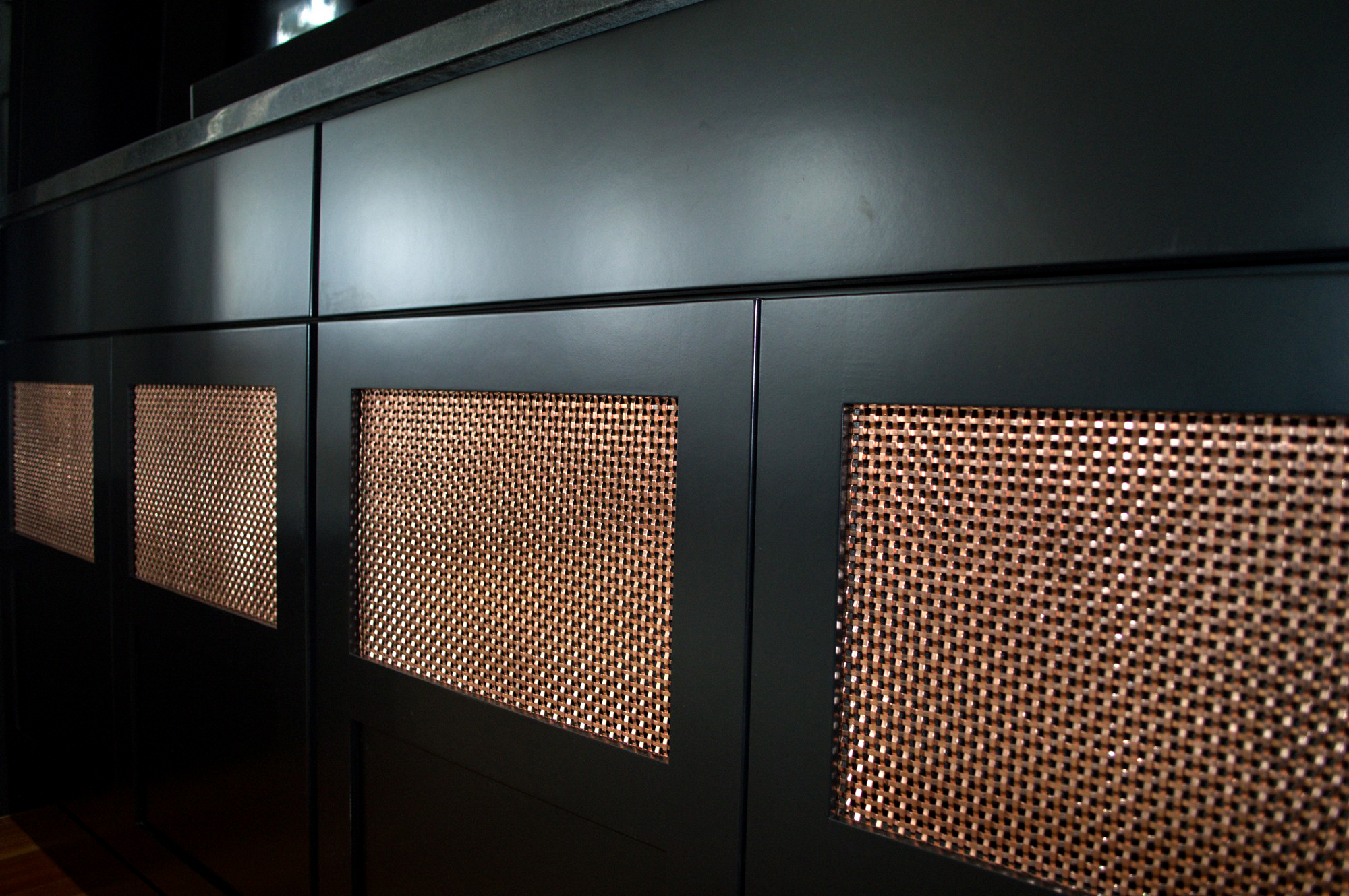 Copper S-16 wire mesh panels in this entertainment center add a modern flare to this rustic home.