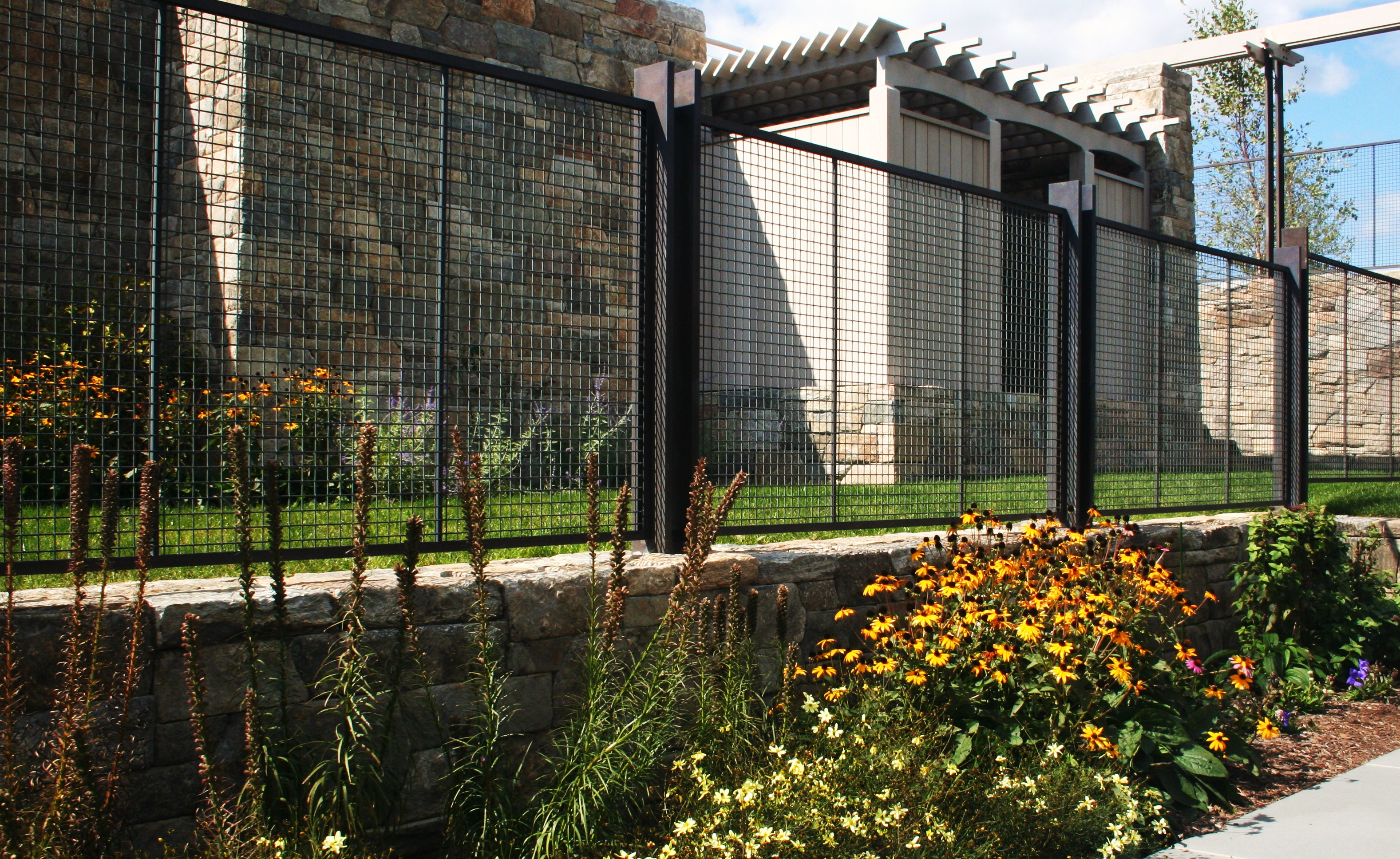 Beautiful bronze woven wire mesh plays off the natural elements of the landscaping.