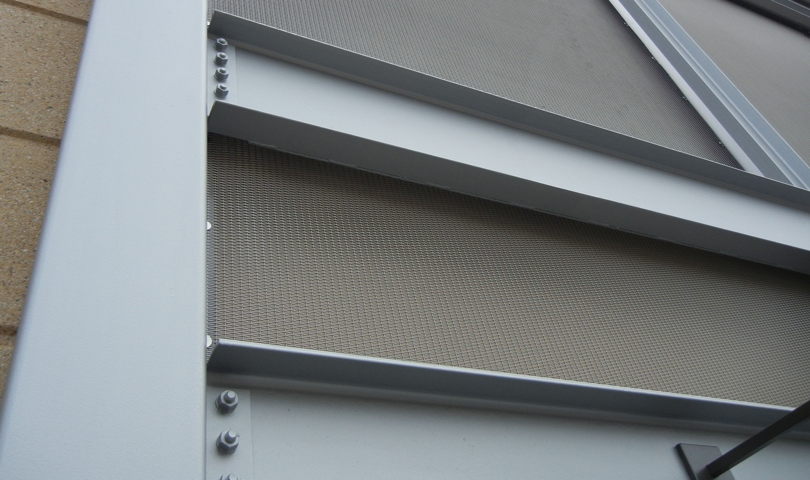 The rectangular plain crimped wire mesh was manufactured to size and were installed using a powder coated angle and bar pressure fit by bolts.