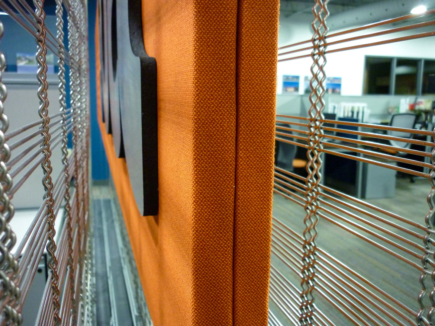 The sign component, fabricated of a sandwich of two sound absorbing panels, occupies the space in between the two panels of woven wire mesh.