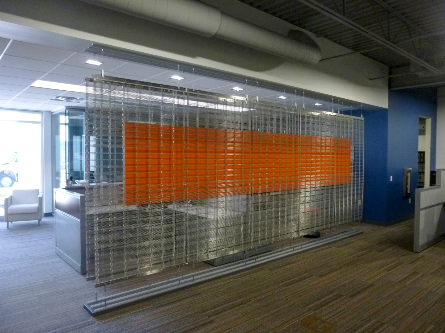 """Banker Wire created a design that incorporates two runs of five 44"""" x 84"""" mesh panels, which are suspended in tension from ceiling-to-floor with stainless steel cables."""