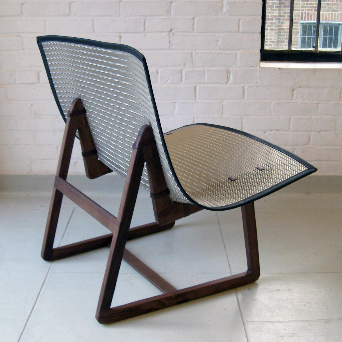 The interaction of dark walnut and metallics create a modern-looking chair.