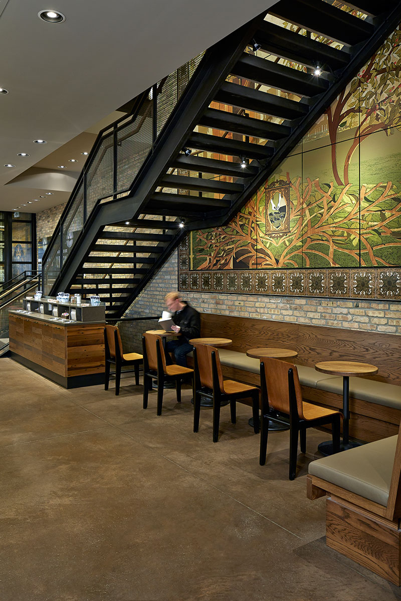 A staircase with Banker Wire railing infill marks the transition between the two levels at this Starbucks flagship store.
