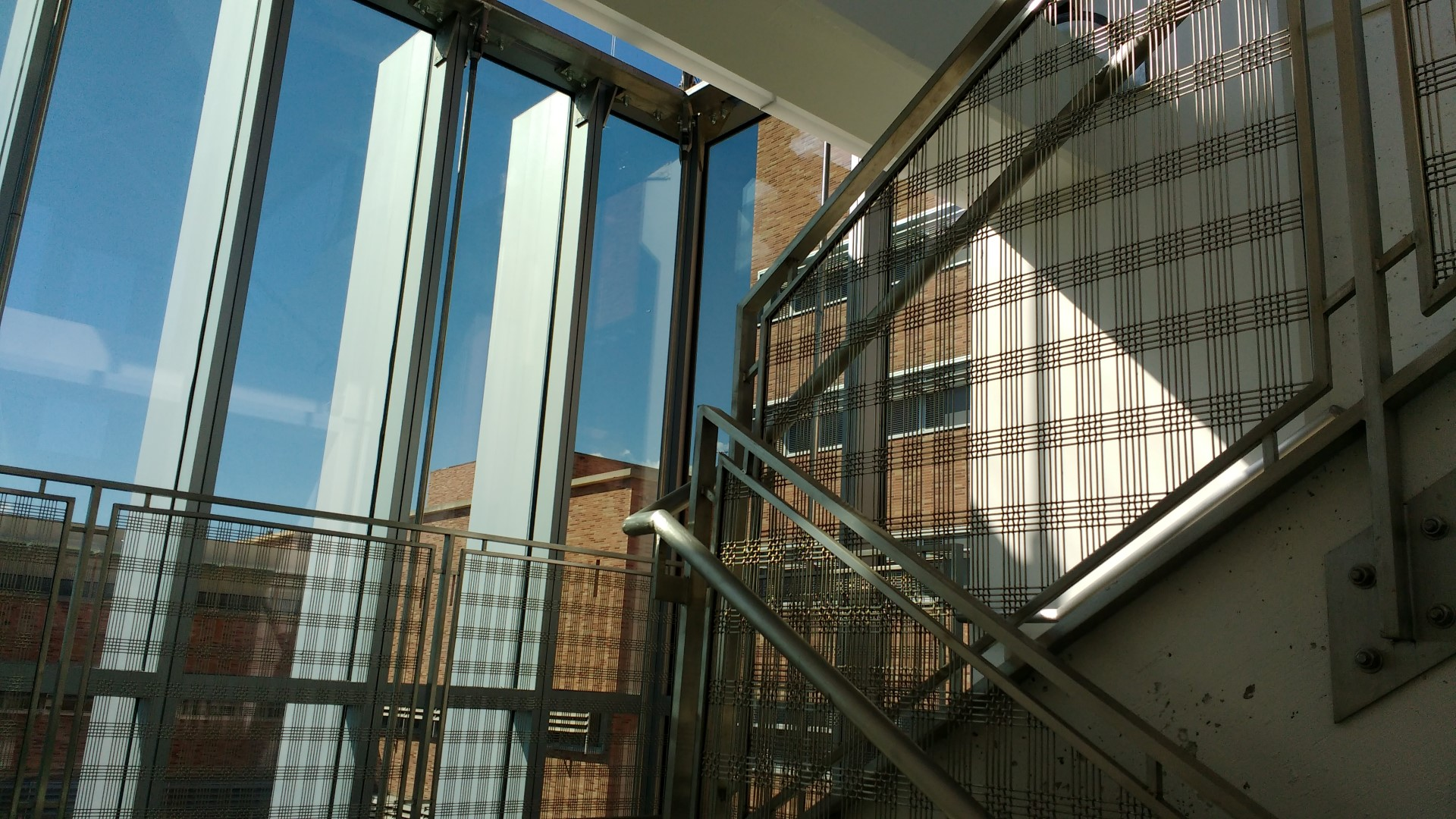 The transparency of the railing infill creates a layered aesthetic between levels on the stiarway.