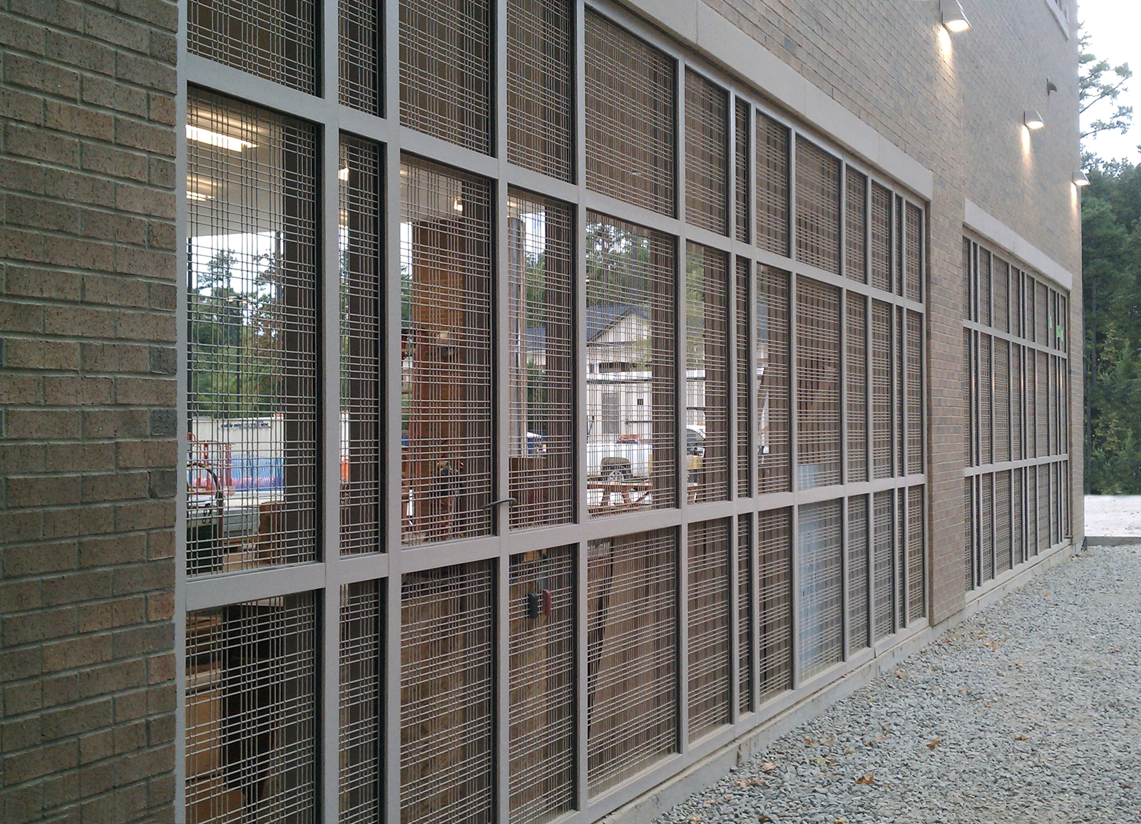 """The wire mesh is framed inside 3/4"""" x 1/8"""" stainless steel frames, then powder coated and fixed to a standard mullion curtain wall."""