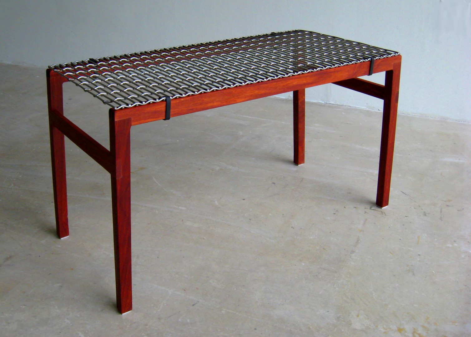 Wood, leather and metal combine form an elegant and sophisticated bench.