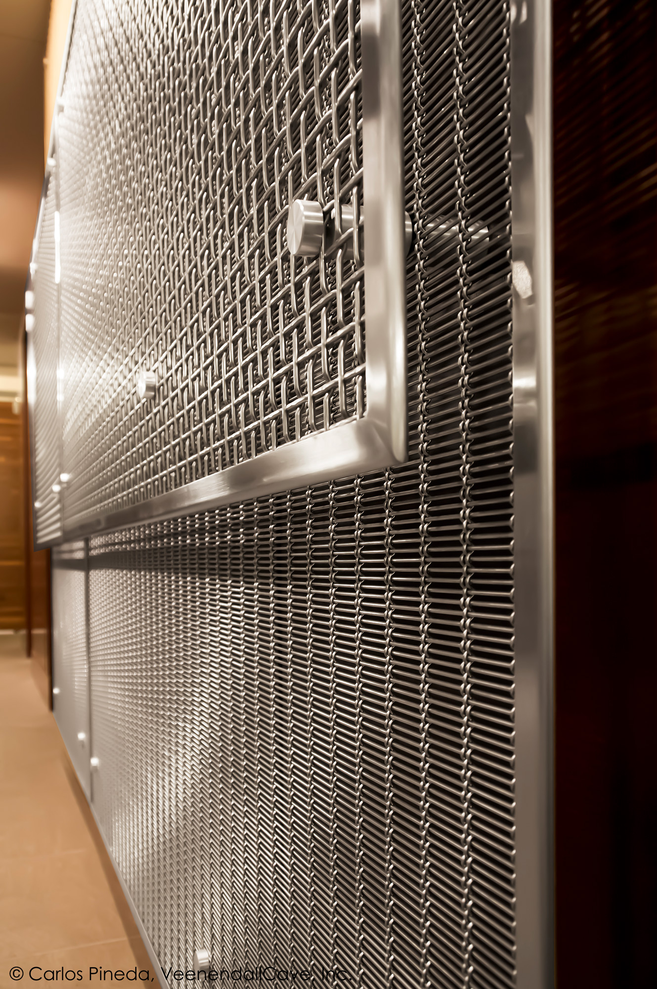 Two different styles of Banker Wire woven wire mesh were layered over mahogany for a contemporary aesthetic.