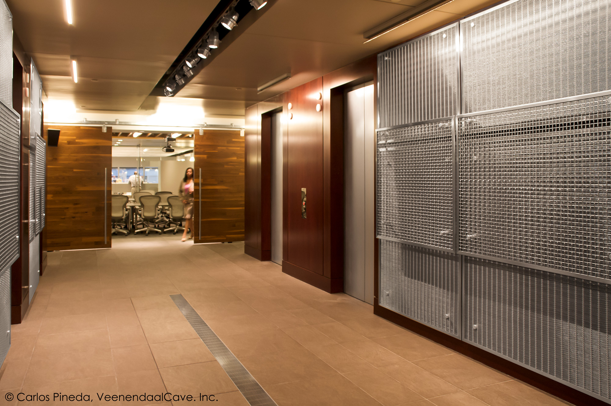 The contrast of the wood and sparkle of the architectural mesh create a unique back drop for this firm's logo.