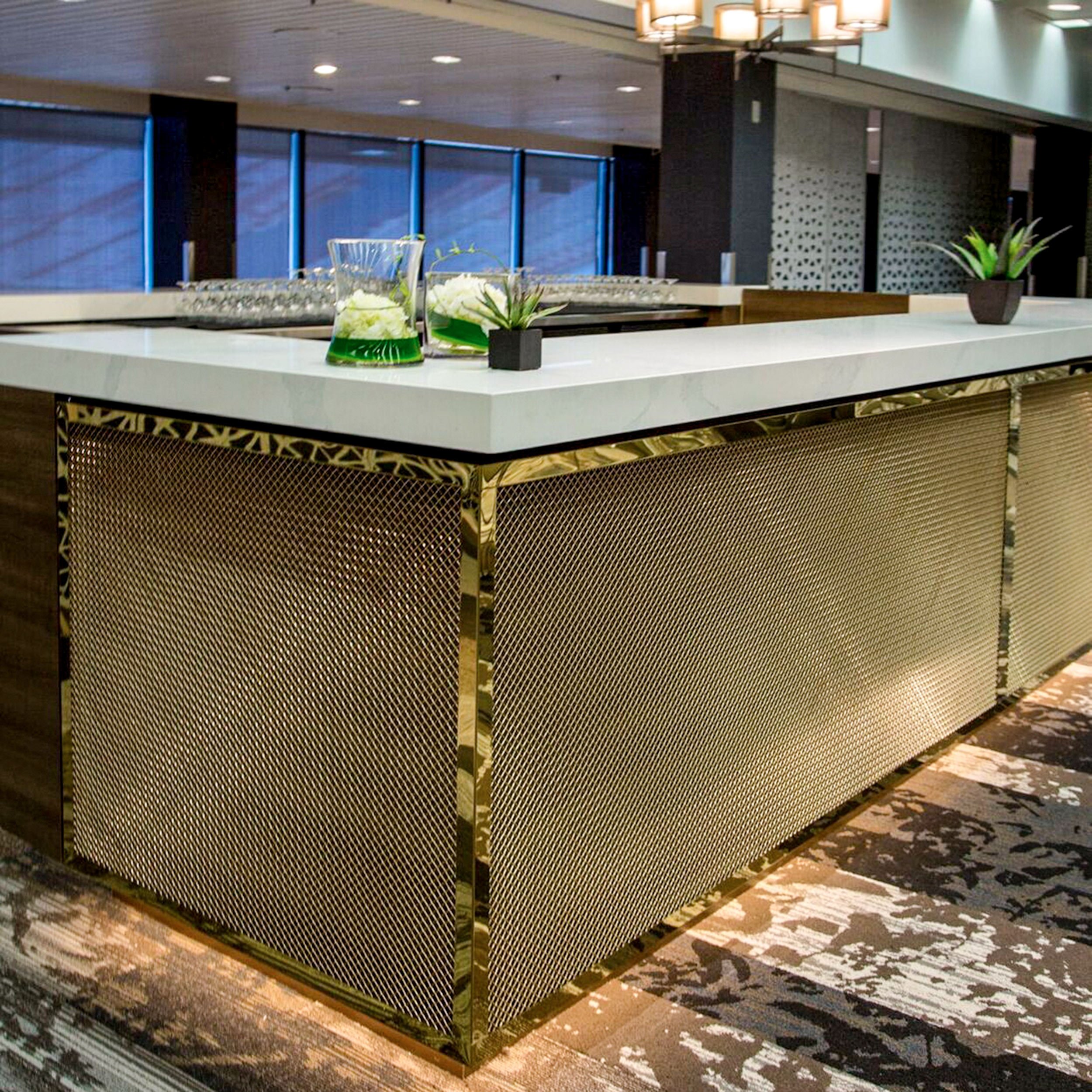 The newly redesigned Red and White club at the University of Calgary features Banker Wire's L-441 in bronze as bar cladding.