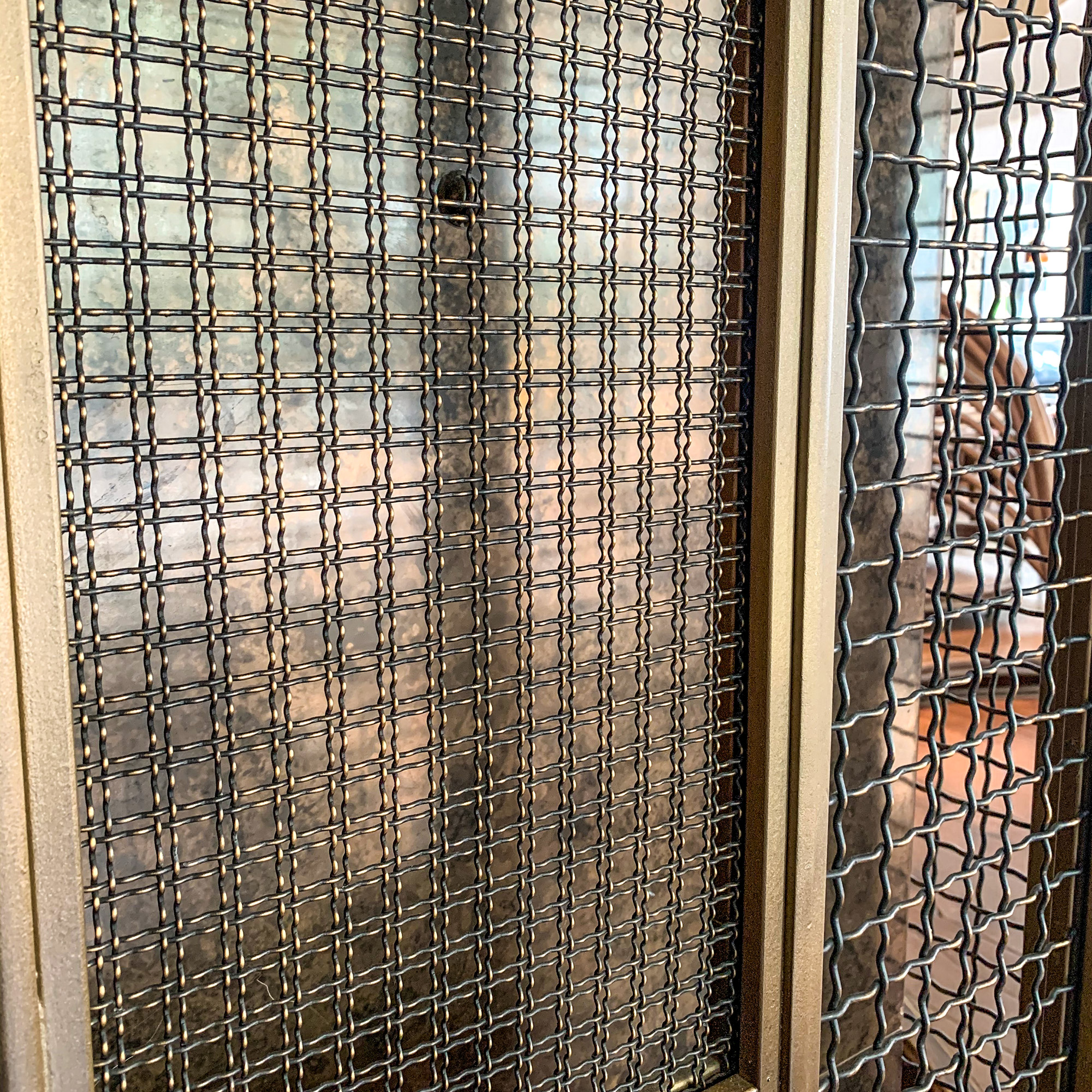 The antique brass secondary finish adds depth and dimension to the cladding using Banker Wire's M22-28 and I-188 woven wire mesh.