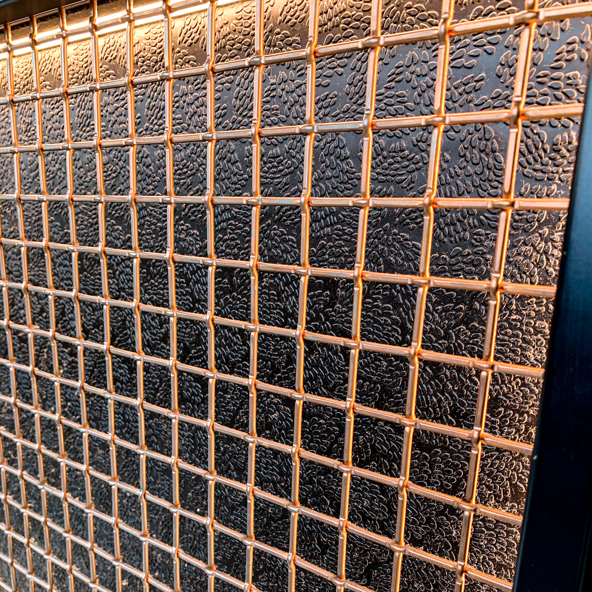 Banker Wire's L-81 in copper stands out against the black of SUSHISAMBA's counters, accented by warm lighting.