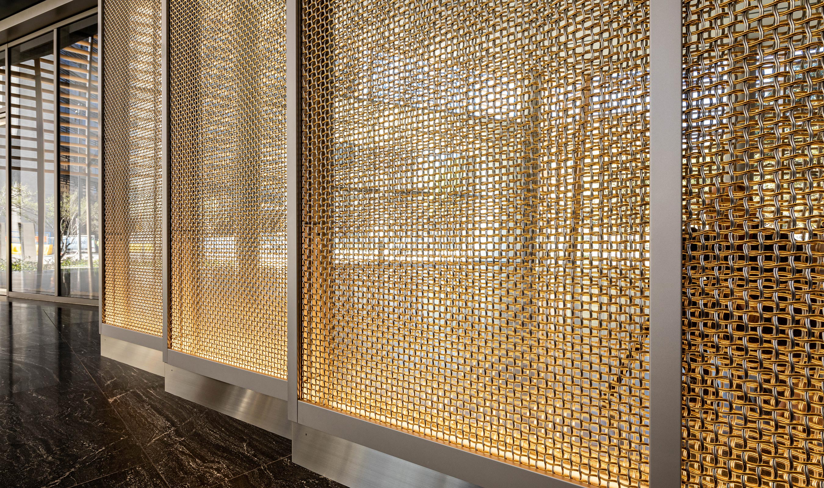 The large open percentage of Banker Wire's M22-80 wire mesh pattern creates a double image reflection in the mirror panels, allowing passersby to appreciate both sides of the nested helical crimped wires.