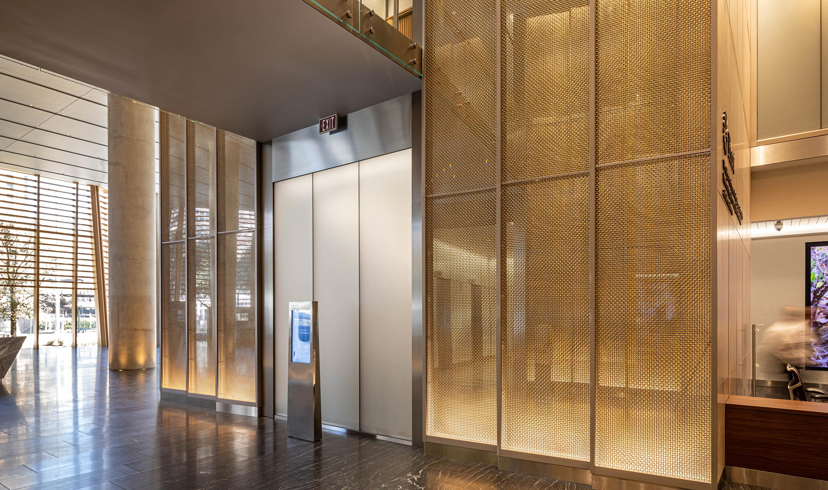 The soft colors of M22-80 in stainless steel and brass compliment the rest of the lobby area at Frost Tower in San Antonio.