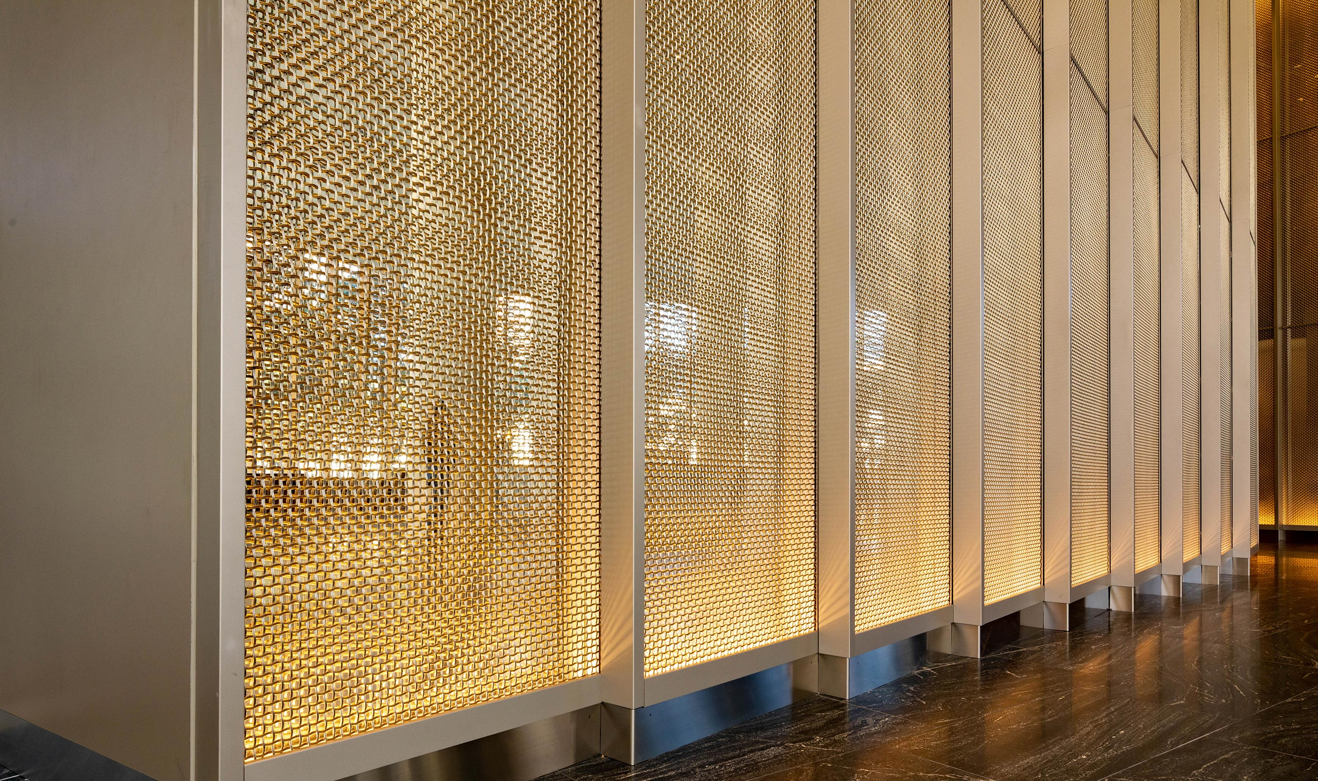 Specialty lighting enchances the visual interest of Banker Wire's M22-80 woven wire mesh in stainless steel and brass.