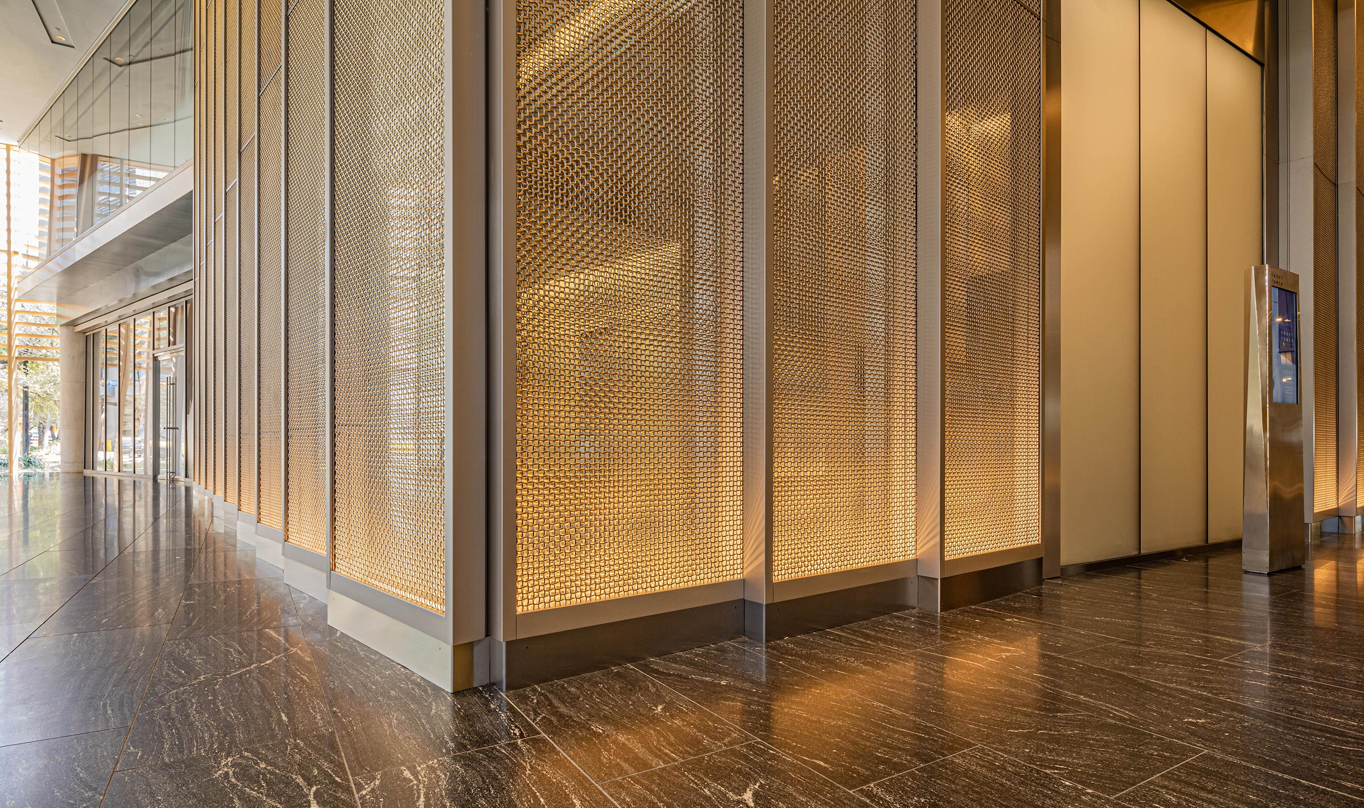 Lighting effects on the feature walls illuminate Banker Wire's M22-80 woven wire mesh.