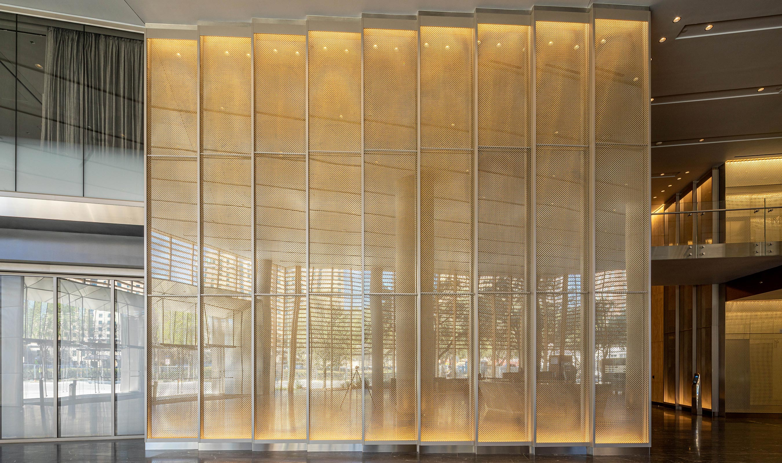 Frost Tower features Banker Wire's M22-80 in stainless steel and brass mixed alloy as cladding on a feature wall in the ground-level entrance lobby.