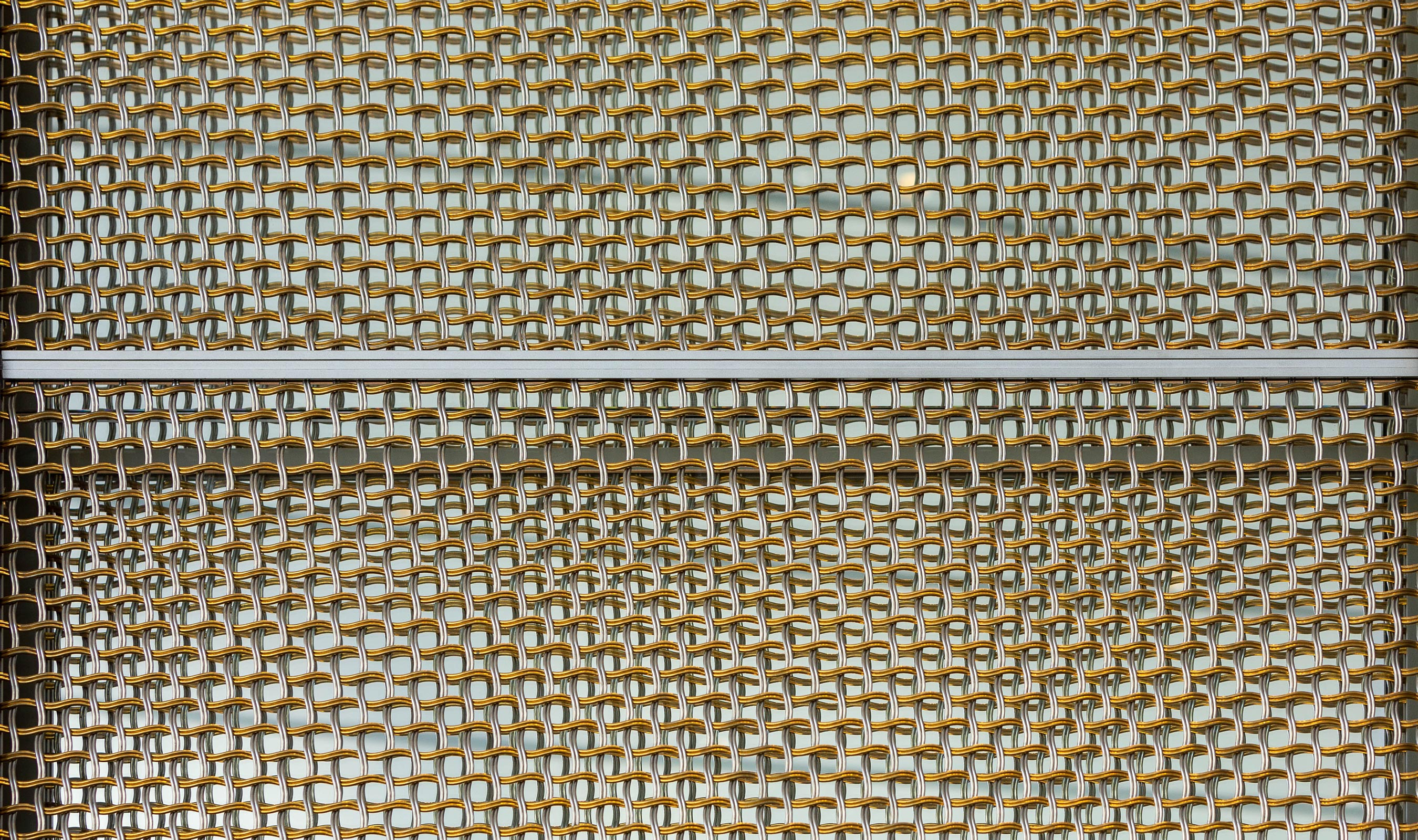 The Banker Wire M22-80 architectural wire mesh pattern uses a pair of nested helical crimped wires to define the circular mesh shape.