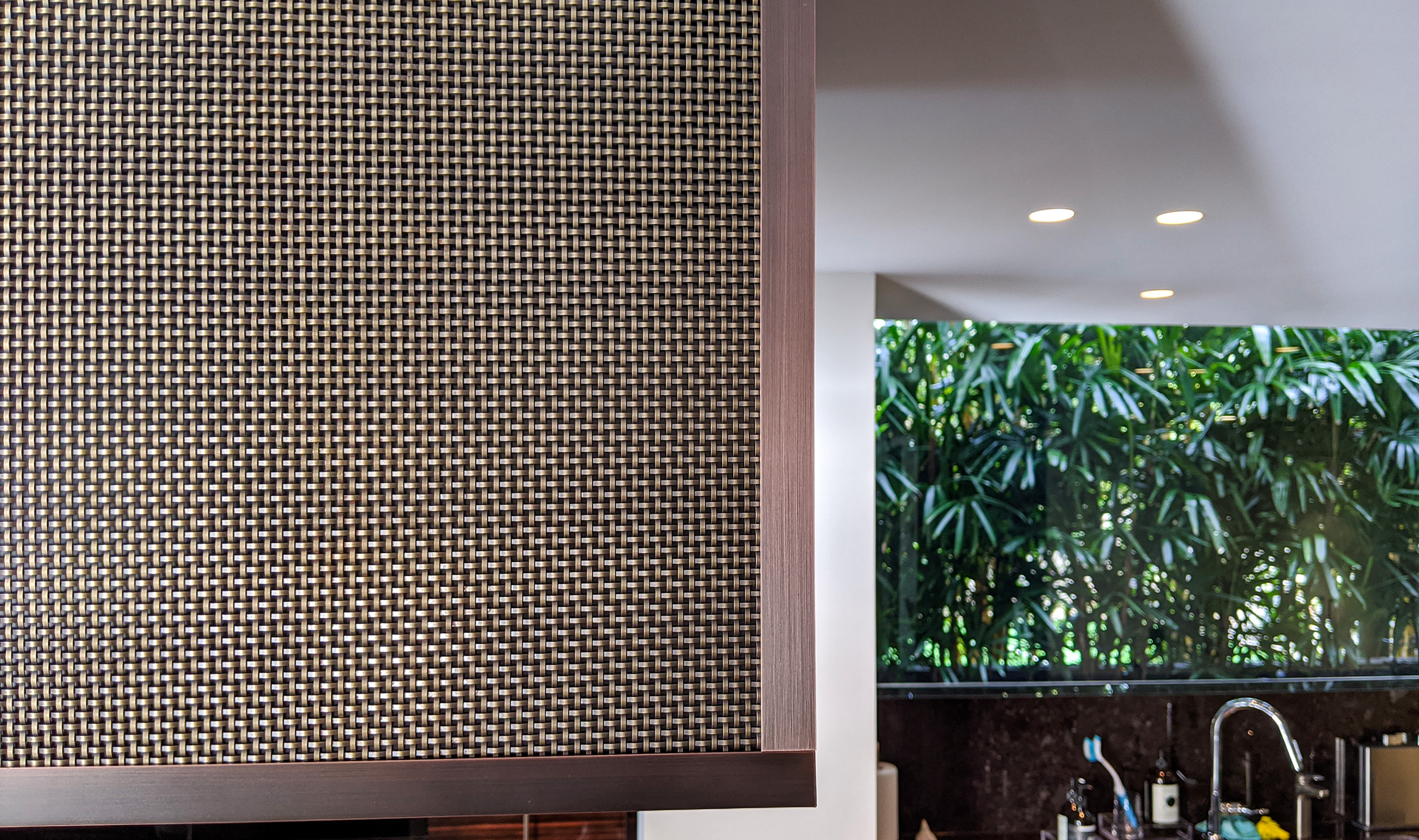 The modern range hood in this Australian home uses Banker Wire's S-32 woven wire mesh plated in Antique Brass.