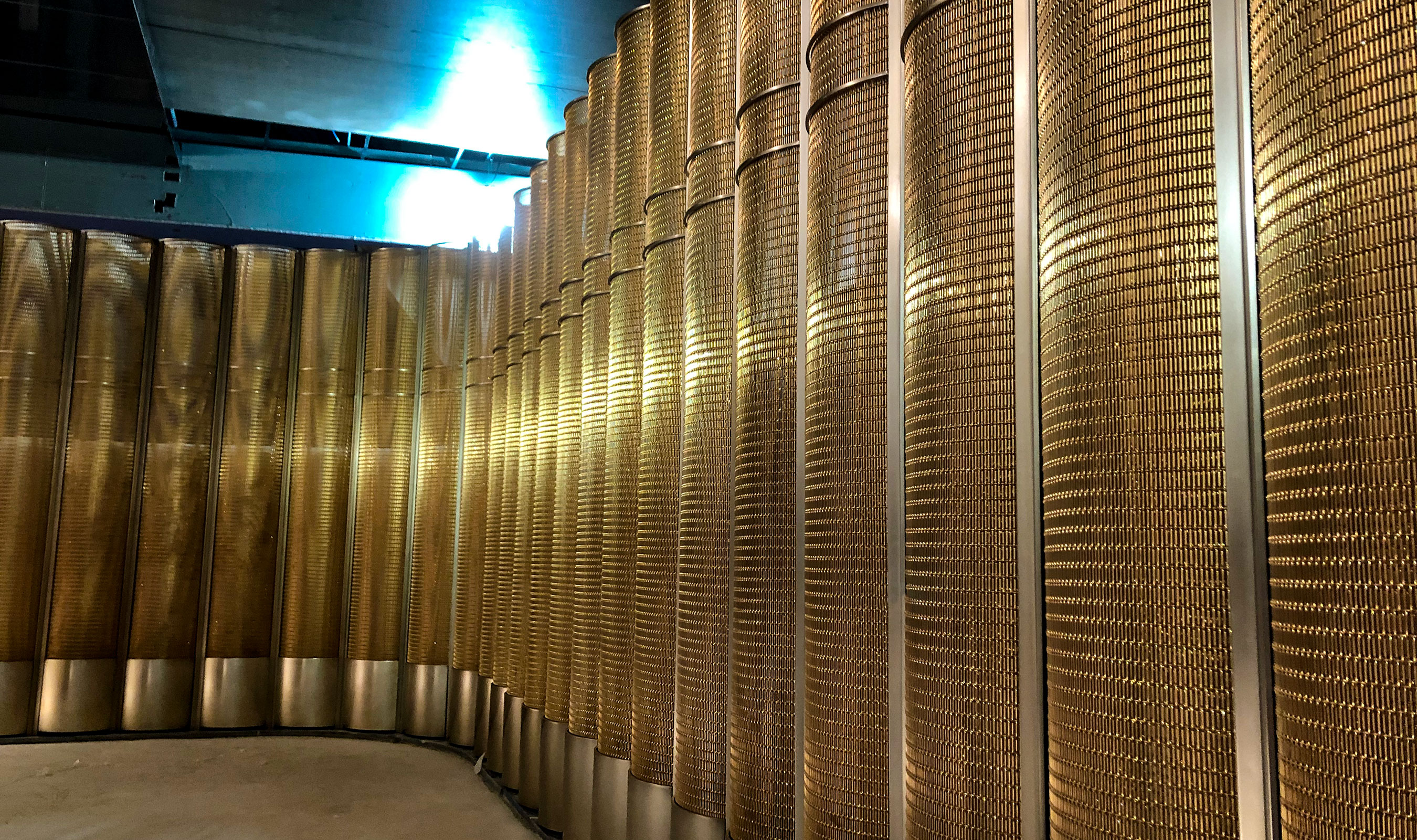 An photo of Banker Wire's SPZ-52 in bronze being installed into the space divider for Peak Restaurant.