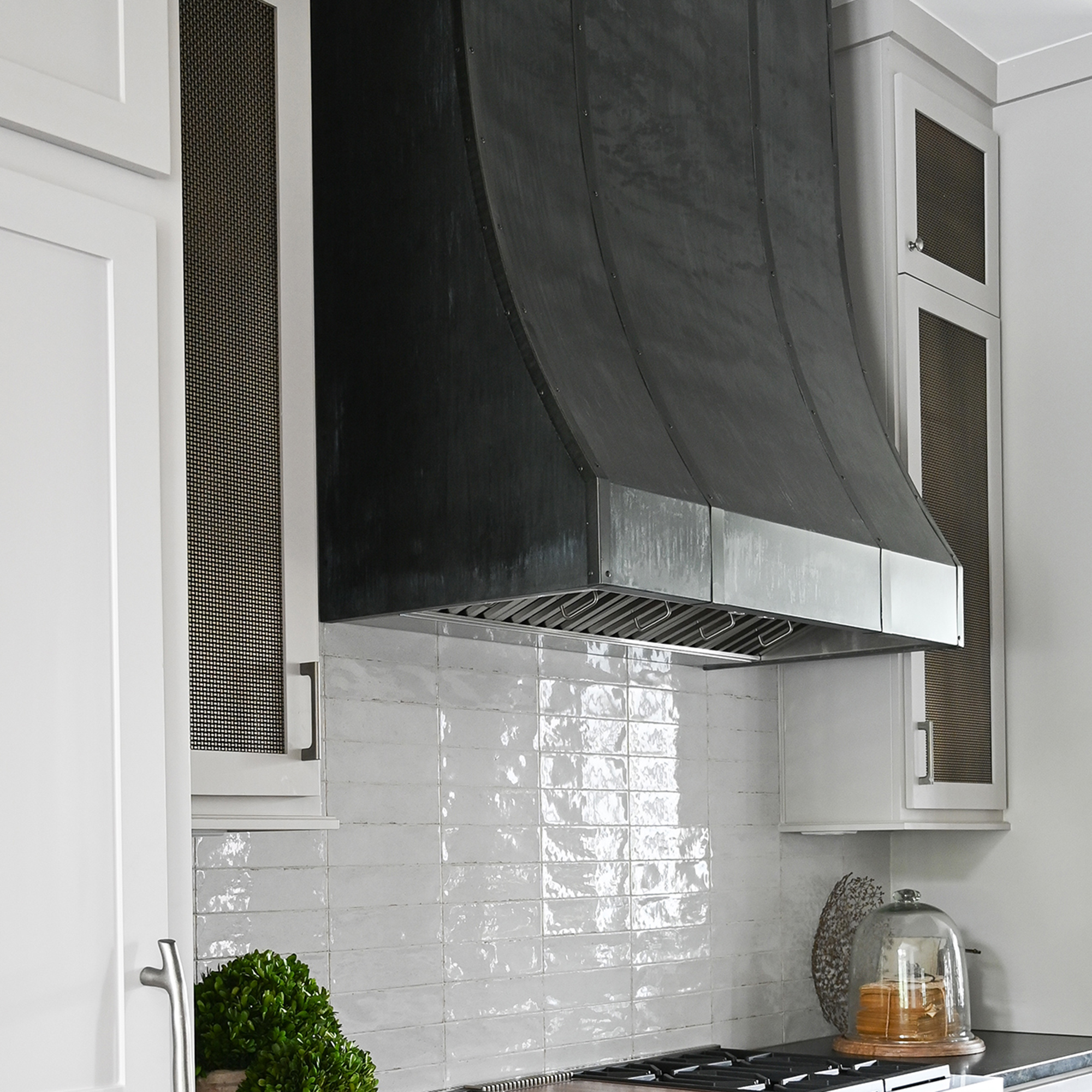 Cabinets filled with woven wire mesh S-12 compliment the metal range hood.