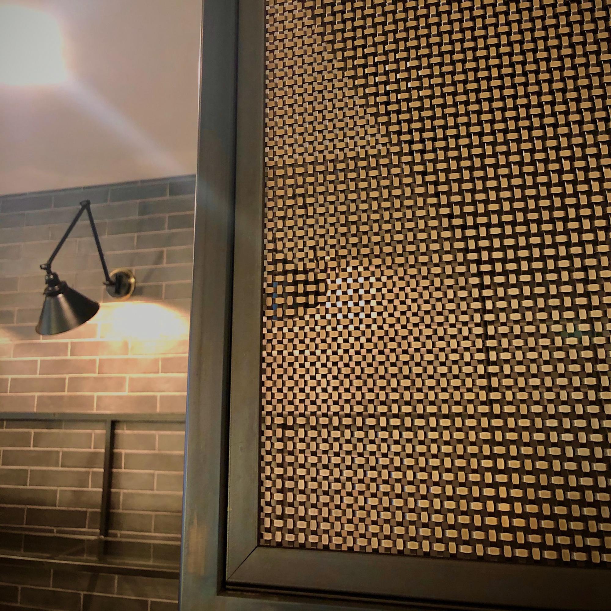 Fine woven wire mesh S-12 creates a near-opaque screen over the shelves.