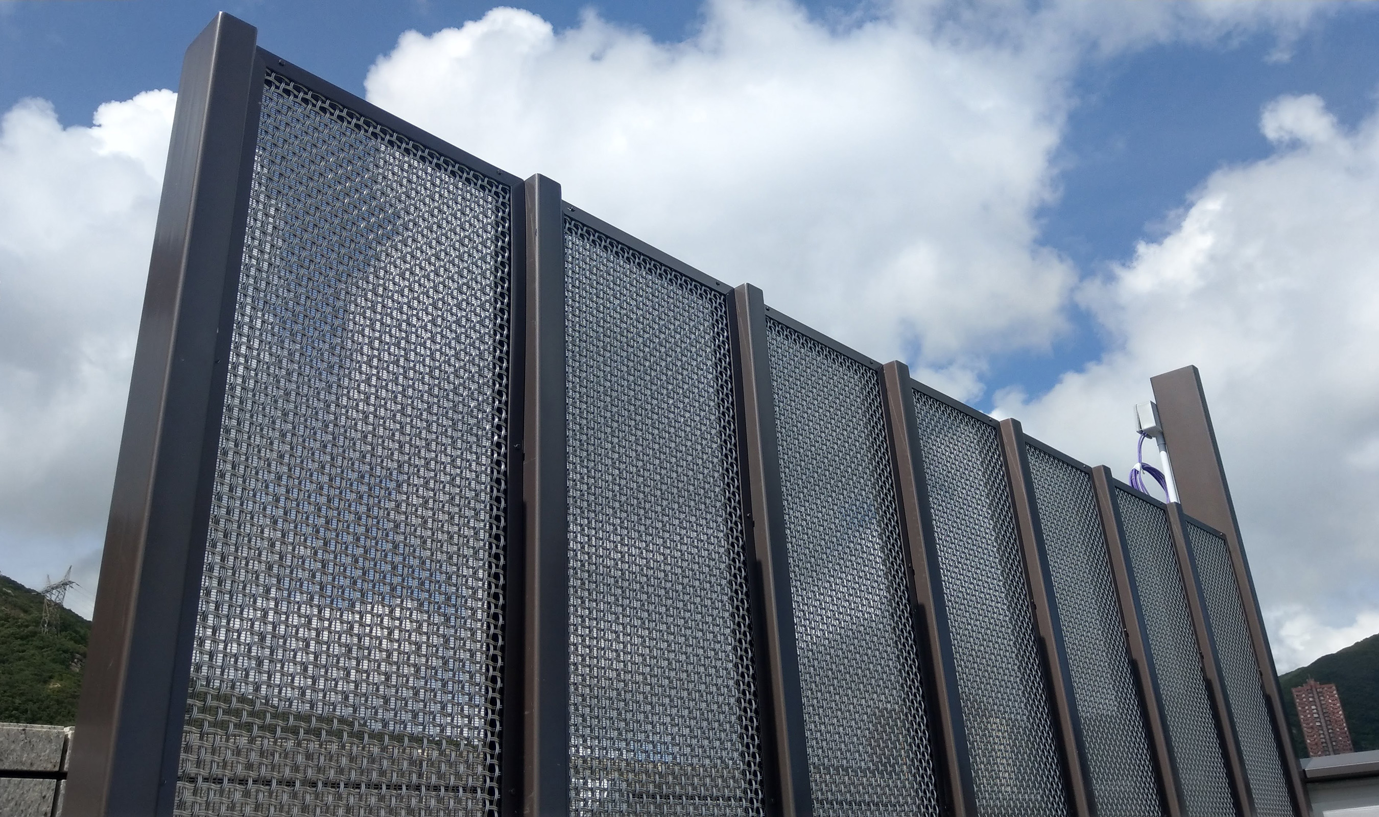 The open-air rooftop as accented with woven wire mesh paneled privacy screens,