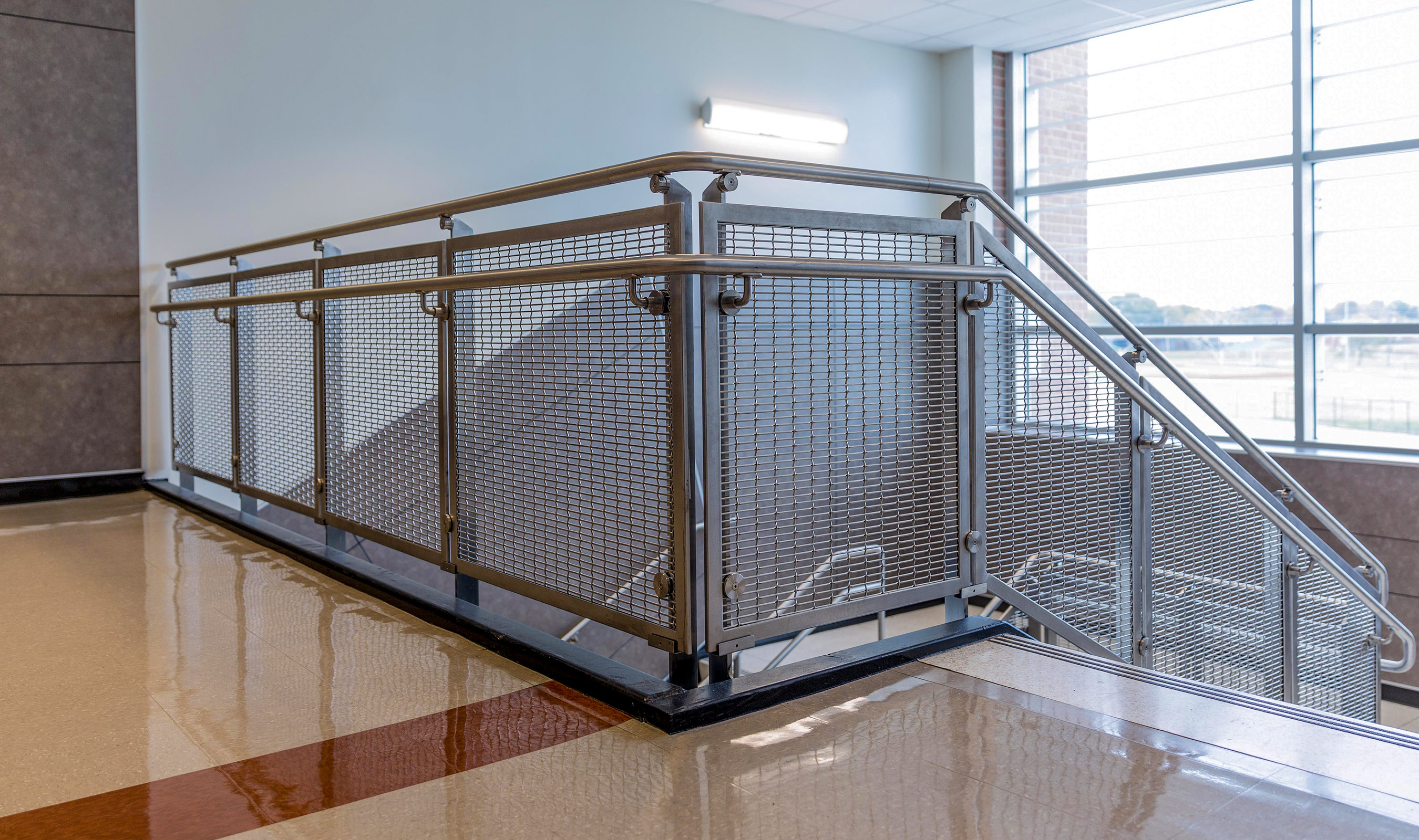 Banker Wire's woven wire mesh in stainless steel as auxiliary stair railing infill.