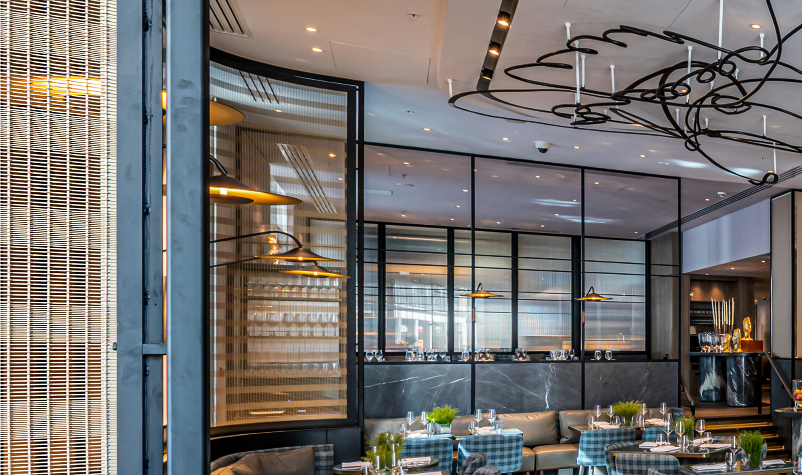 The woven wire mesh space dividers in this London restaurant add to the luxury ambiance of the space.
