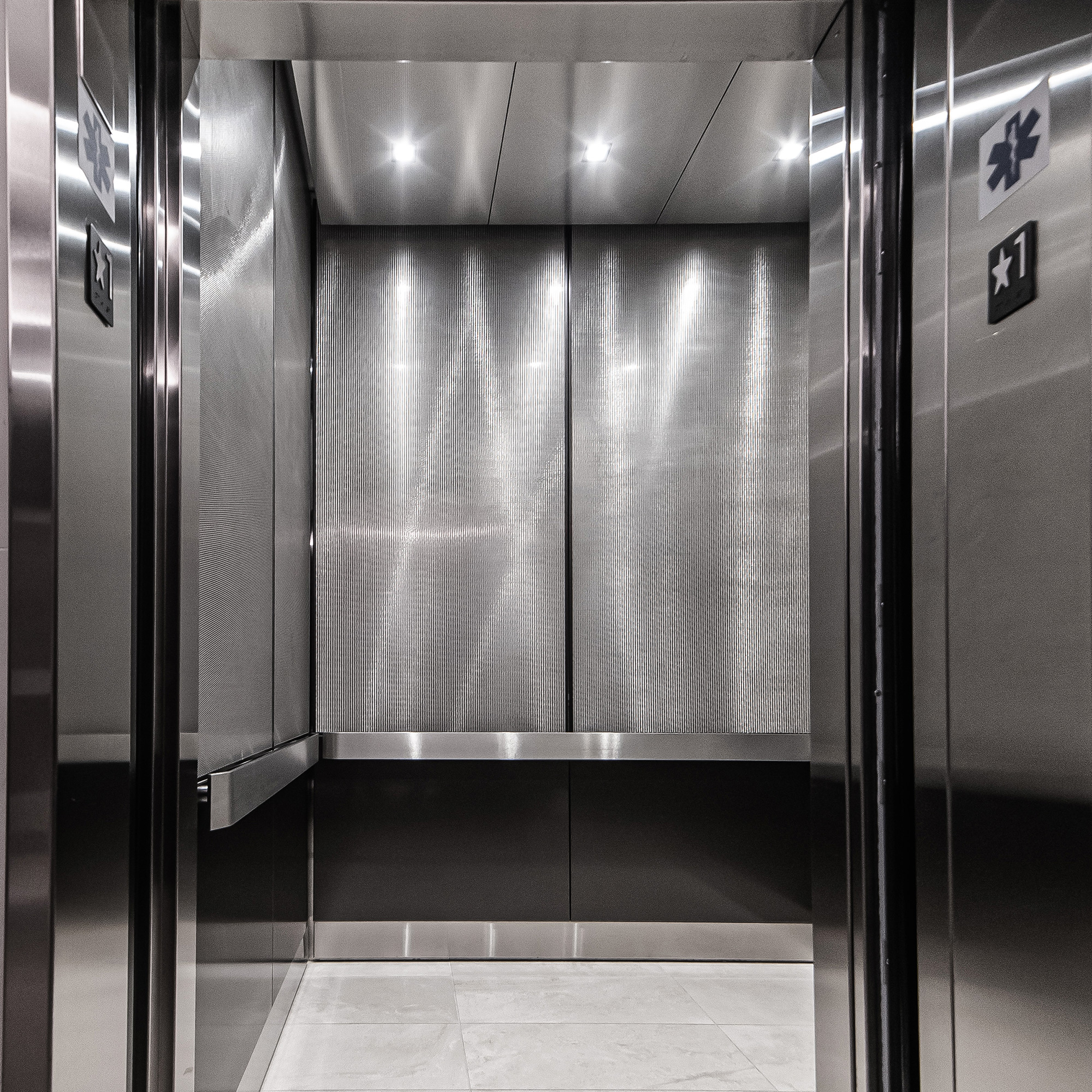The monochromatic tones of the elevator interior present a modern aesthetic.